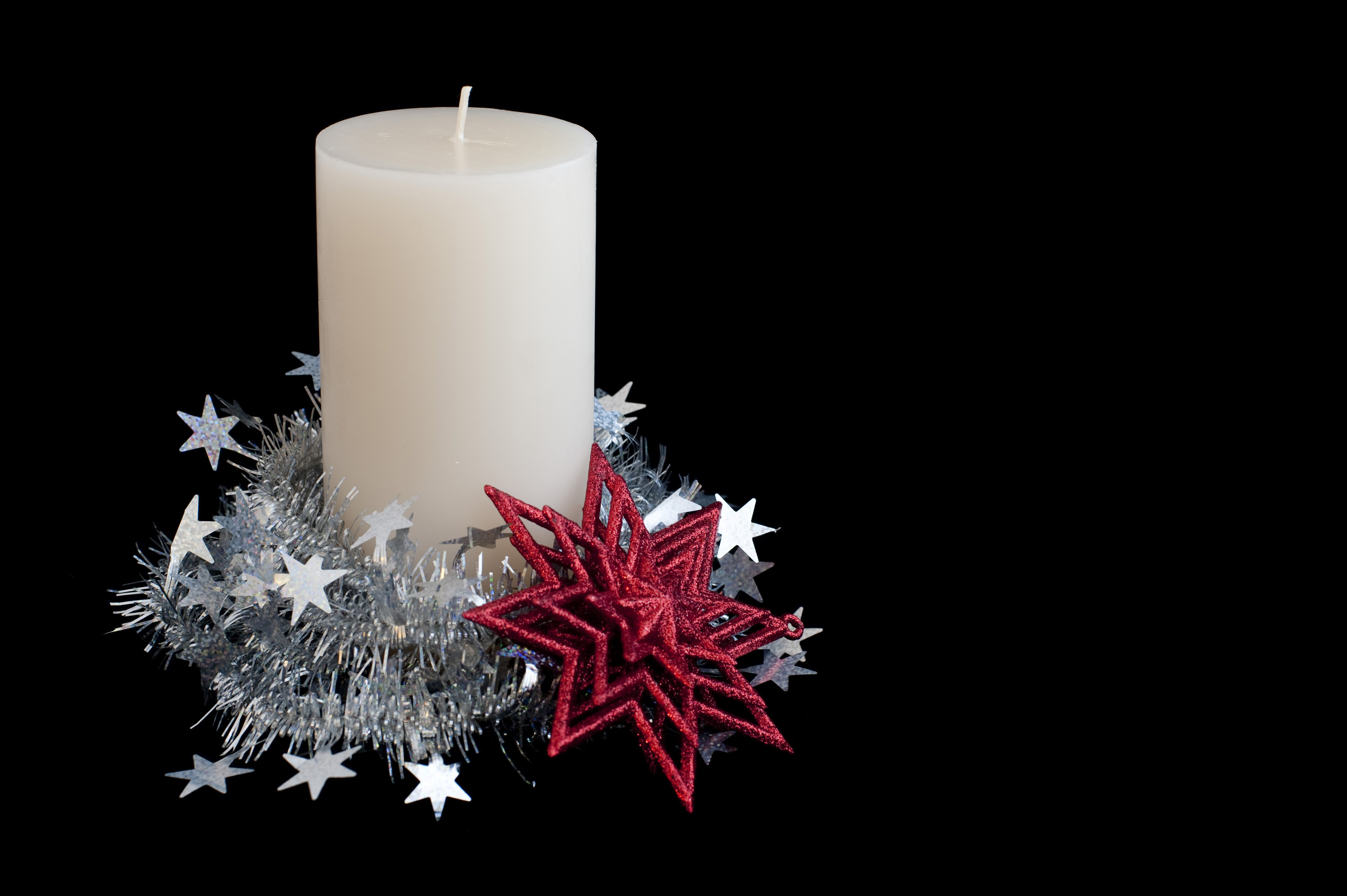 a christmas candle and star wrapped in tinsel on a black background