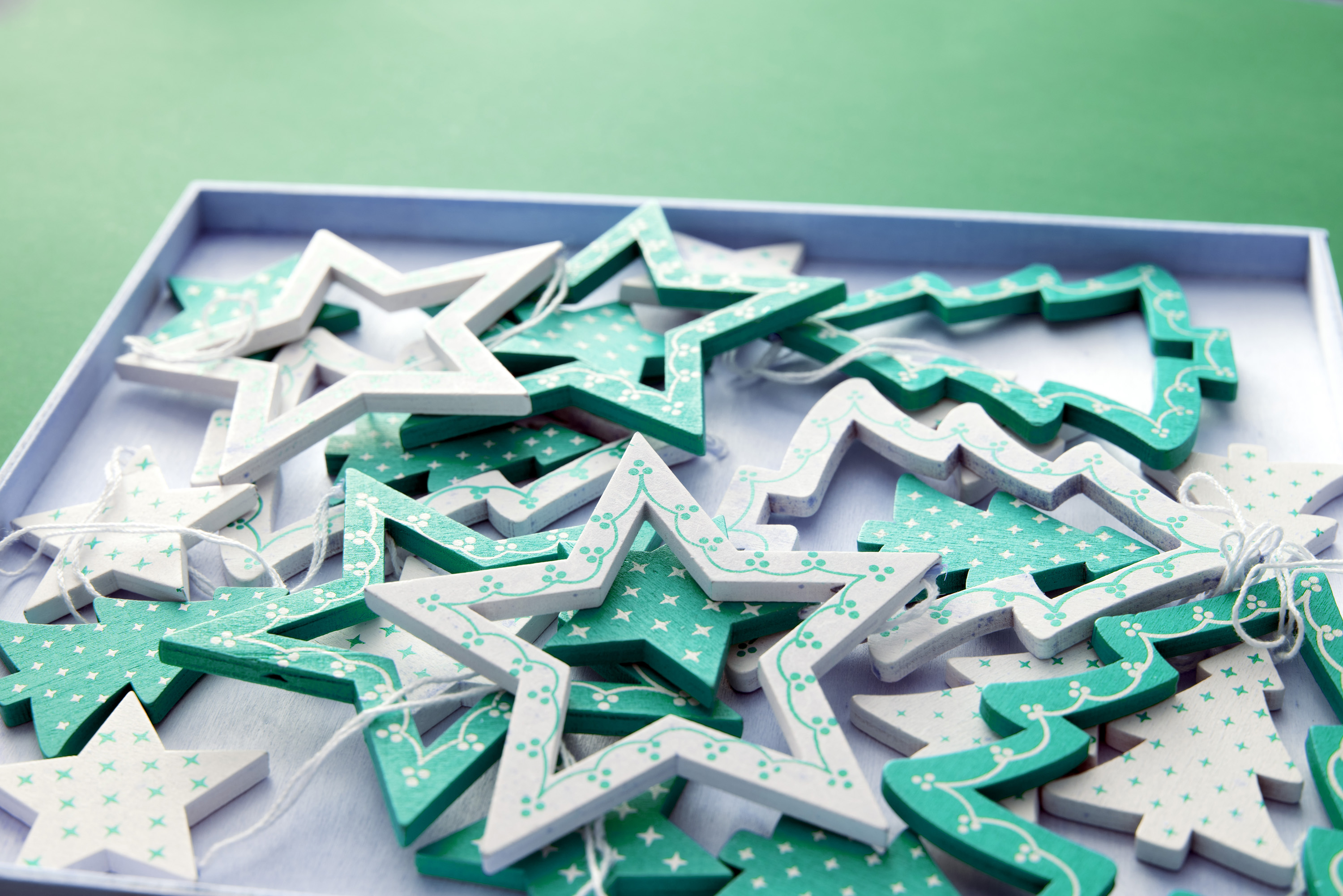 Tray of wooden green star and tree-shaped ornaments for hanging on the Christmas tree over a green background