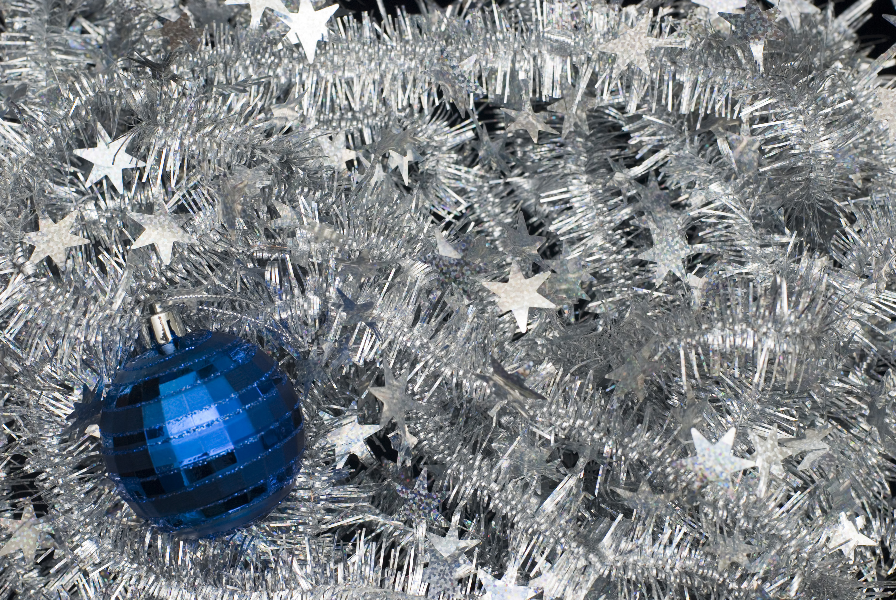 a bed of silver tinsel with a blue christmas bauble