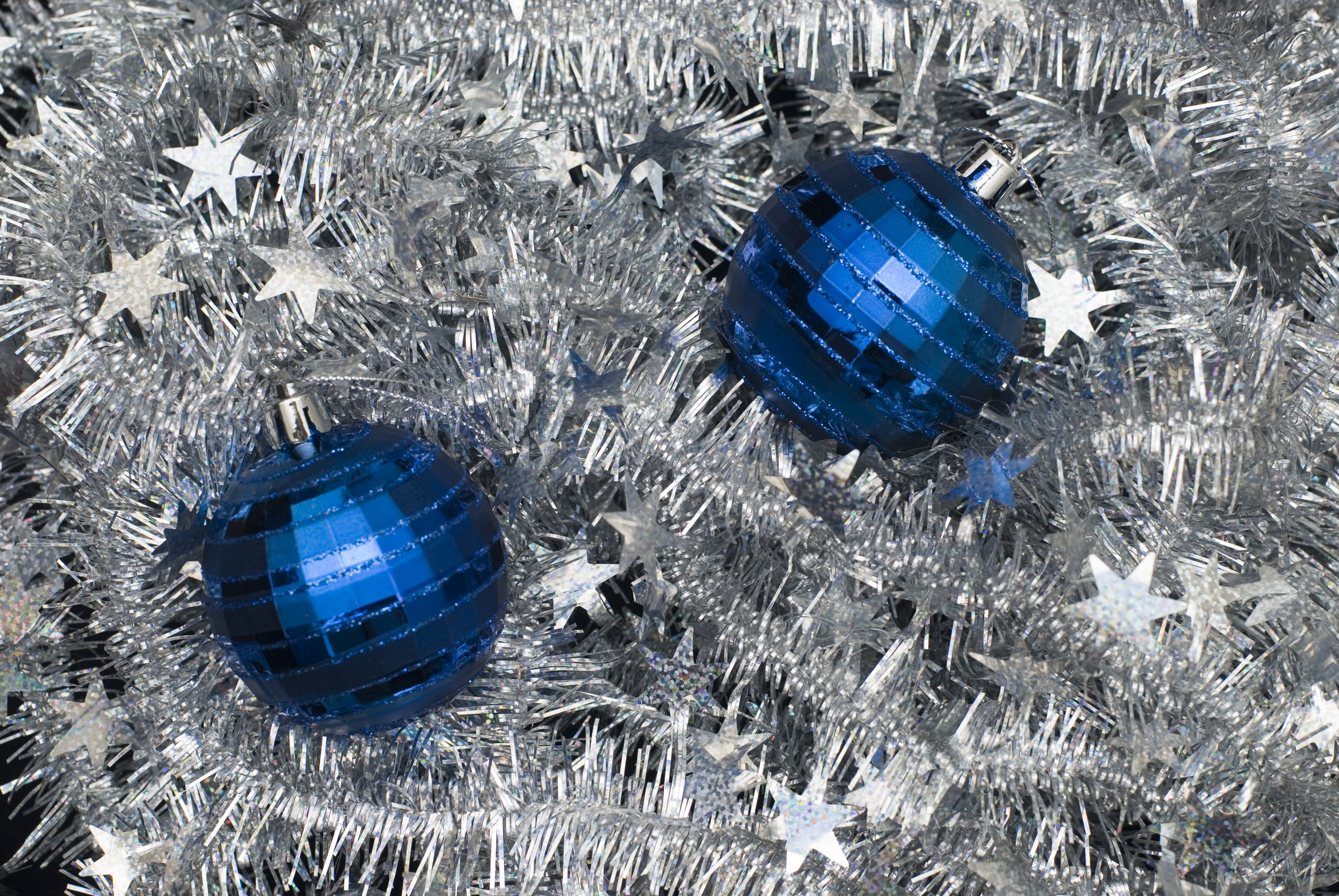 a bed of silver tinsel with blue christmas baubles on top