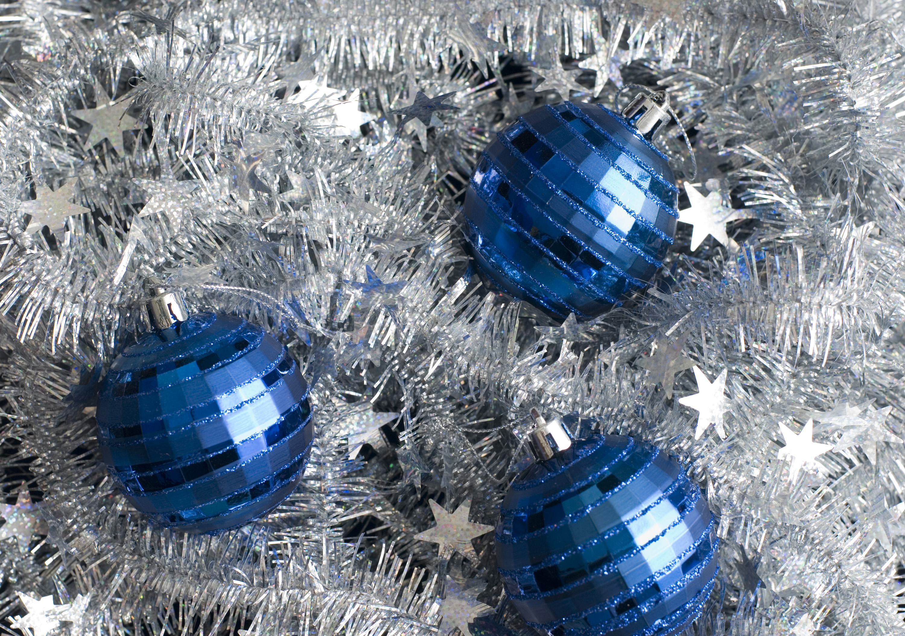 a bed of silver tinsel with three blue christmas baubles
