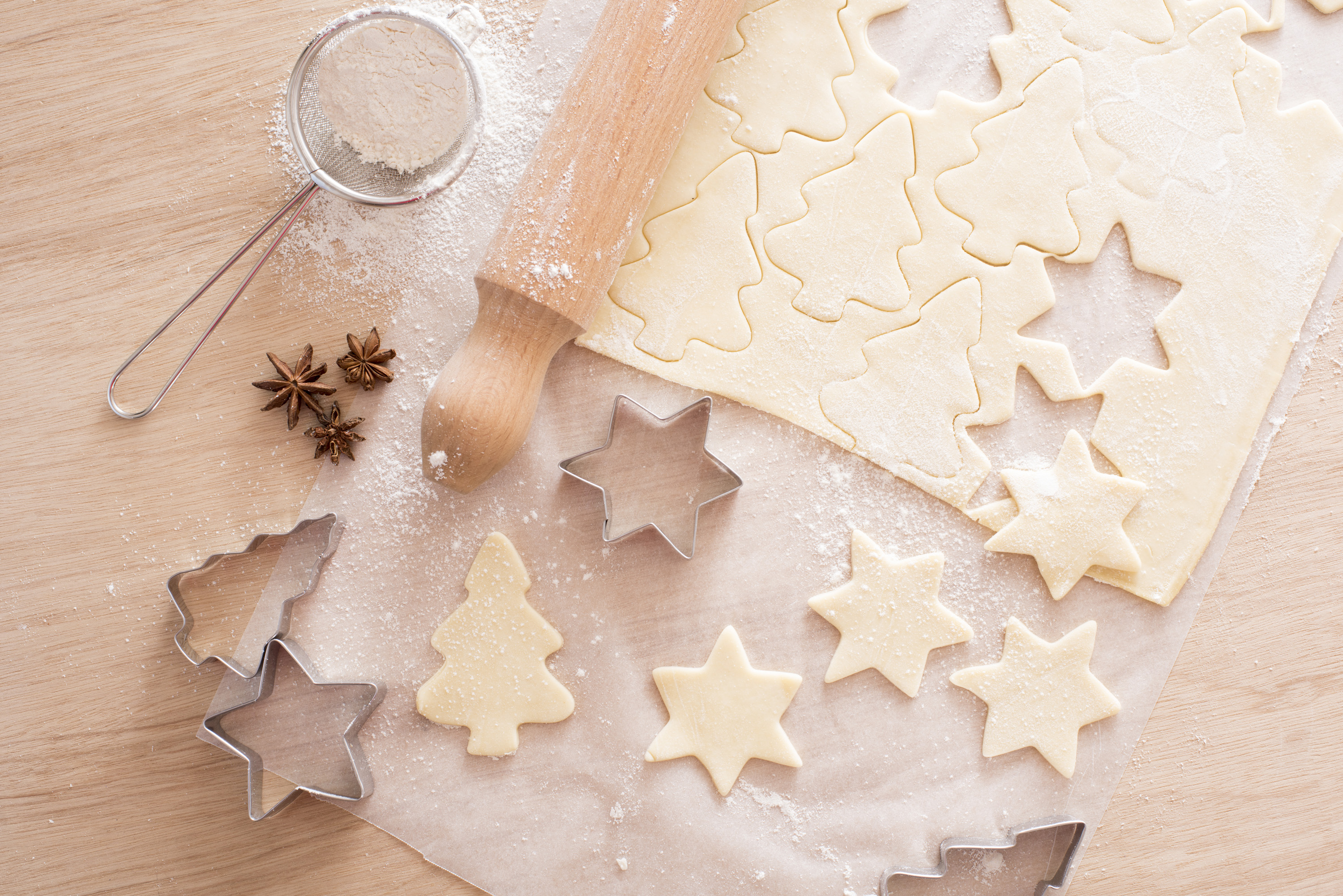 Baking traditional spicy Christmas biscuits with uncooked pastry cut into tree and star shapes alongside metal cookie cutters, rolling pin, sieve and star anise spice, overhead view