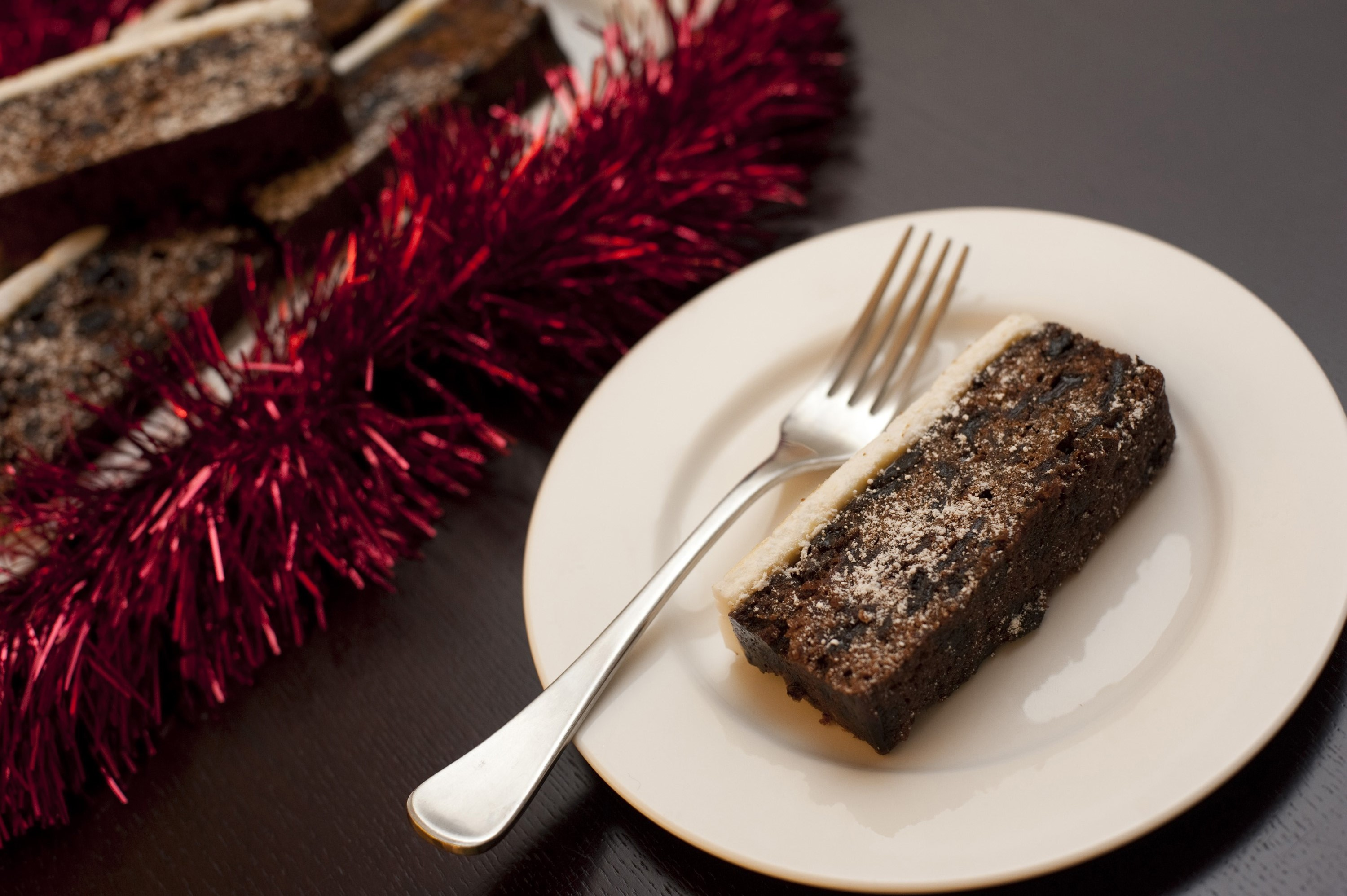 Slice of Christmas fruit cake with a marzipan and almond paste icing served on a plate on a festive table, high angle view