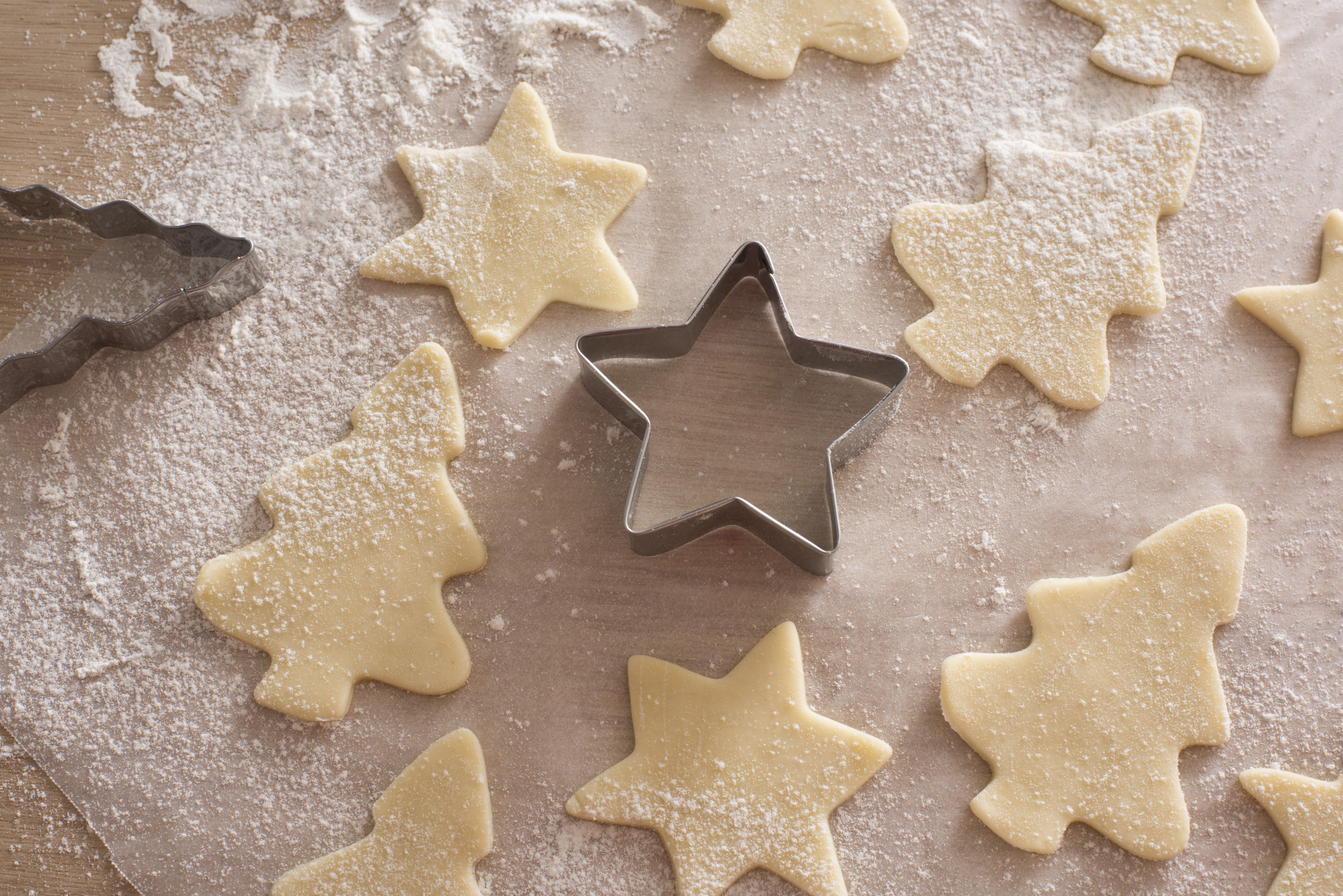 Fresh cookie dough in shapes of Christmas holiday theme stars and trees ready to bake