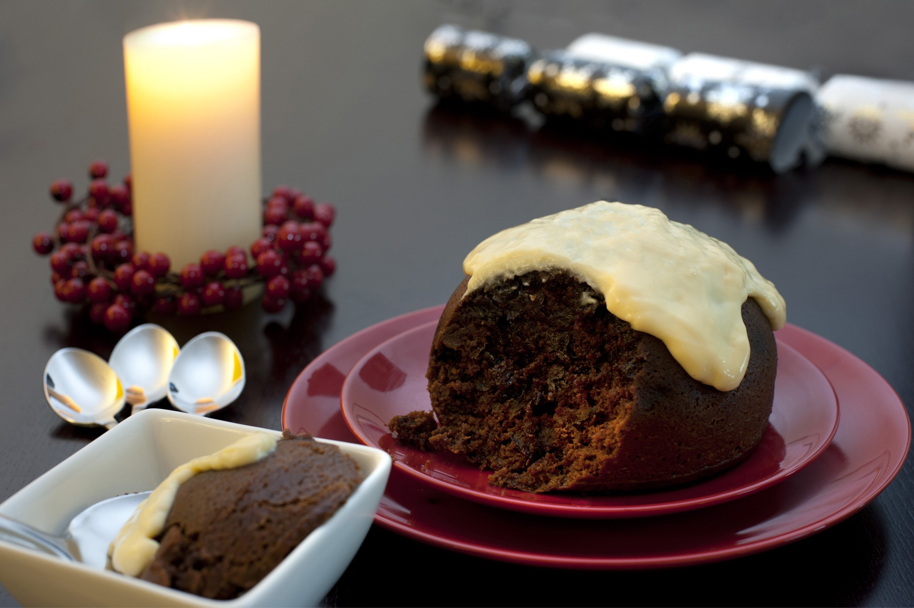 Delicious fruity Christmas pudding with a brandy sauce topping and a serving in a bowl alongside on a festive Christmas table
