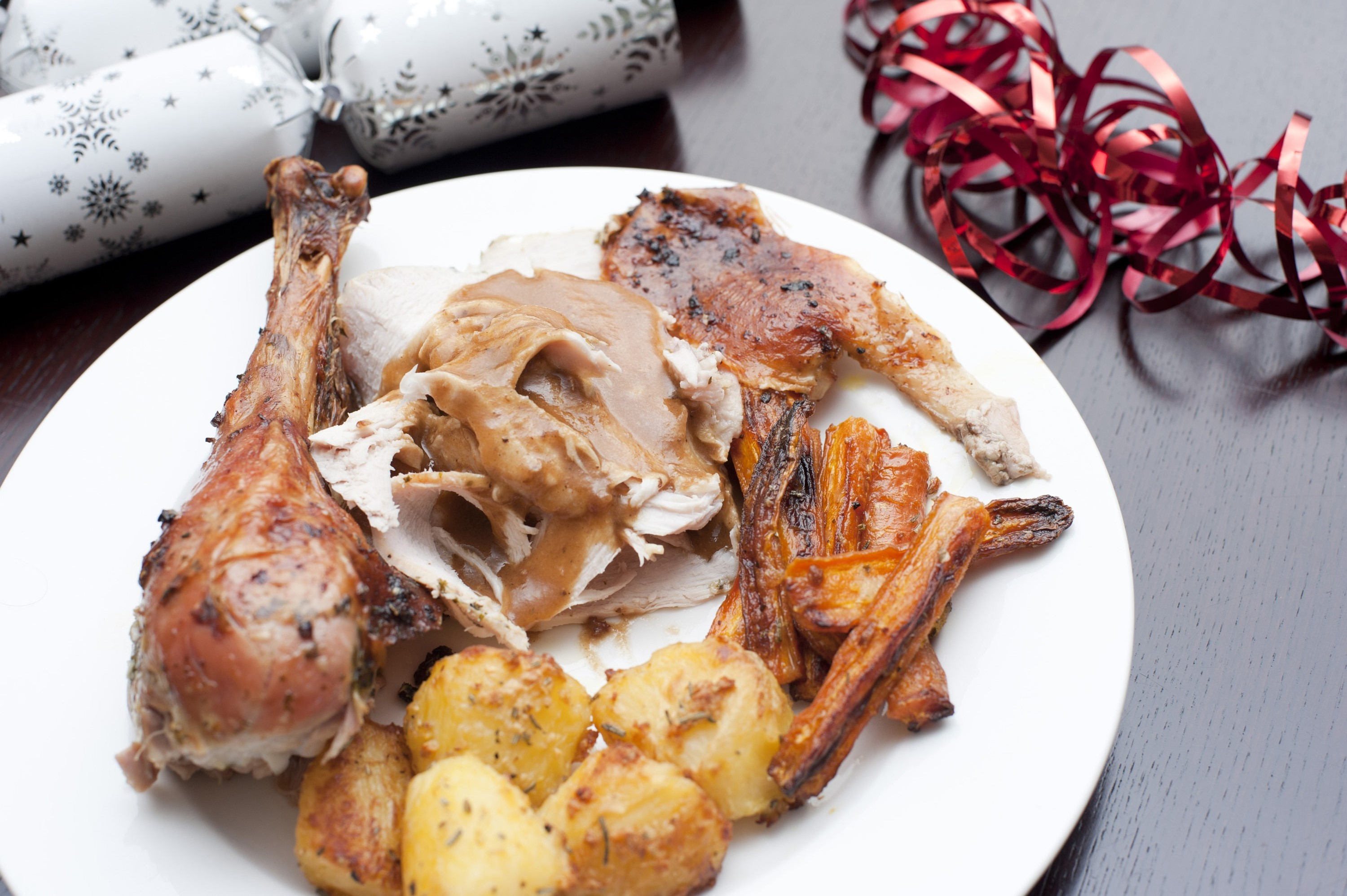 Serving of festive roast turkey topped with gravy with roasted potatoes and carrots for celebrating a Christmas dinner on a table with Christmas crackers