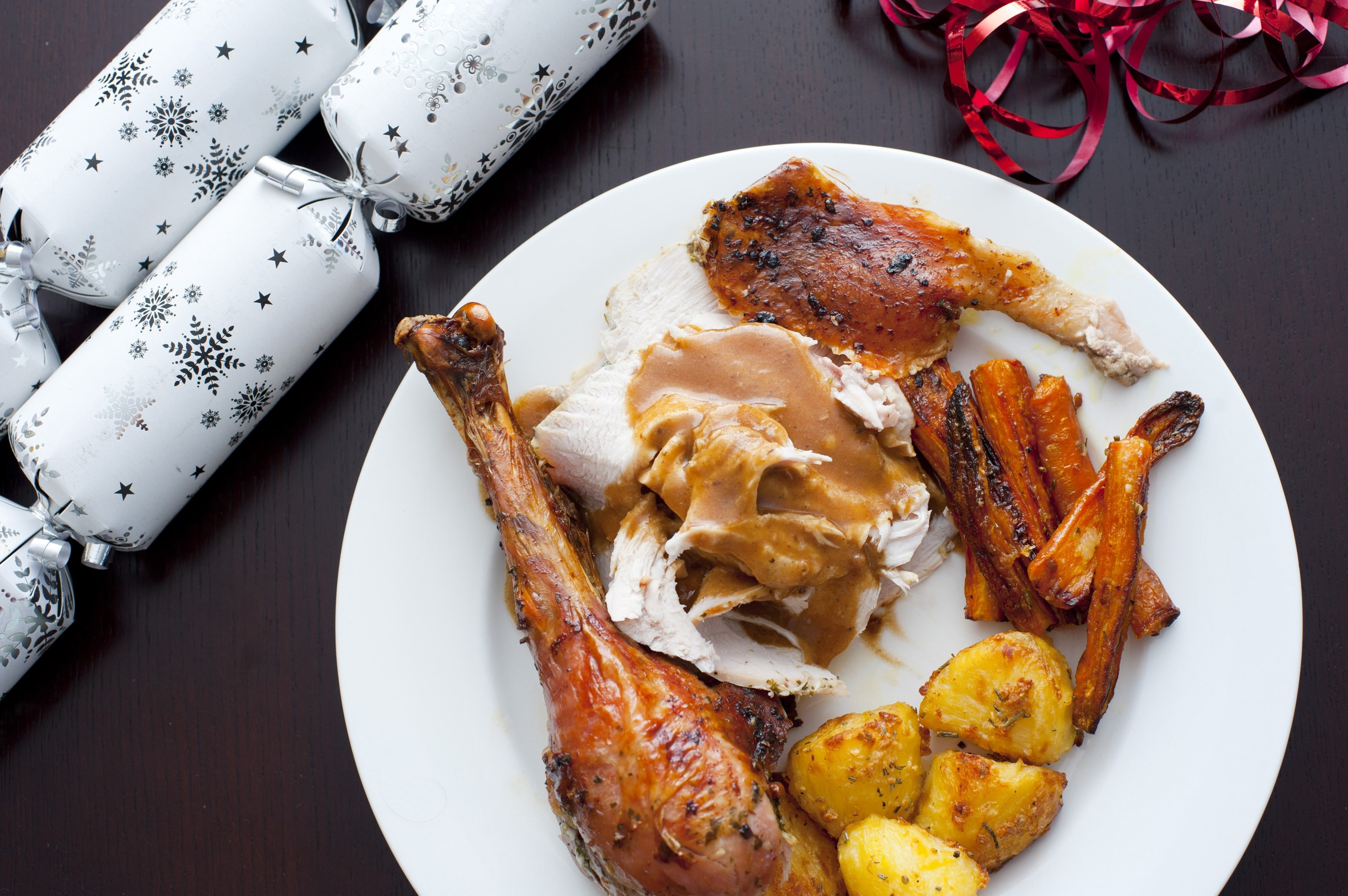 Tasty roast Christmas dinner with turkey, potatoes and carrots topped with gravy, overhead view
