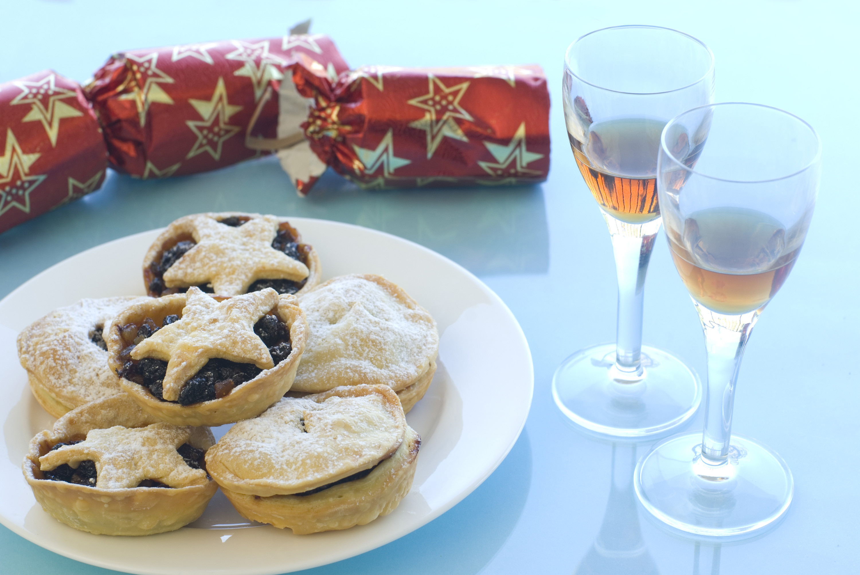 a plate of christmas mincemeat pies and with of sherry and a pulled christmas cracker