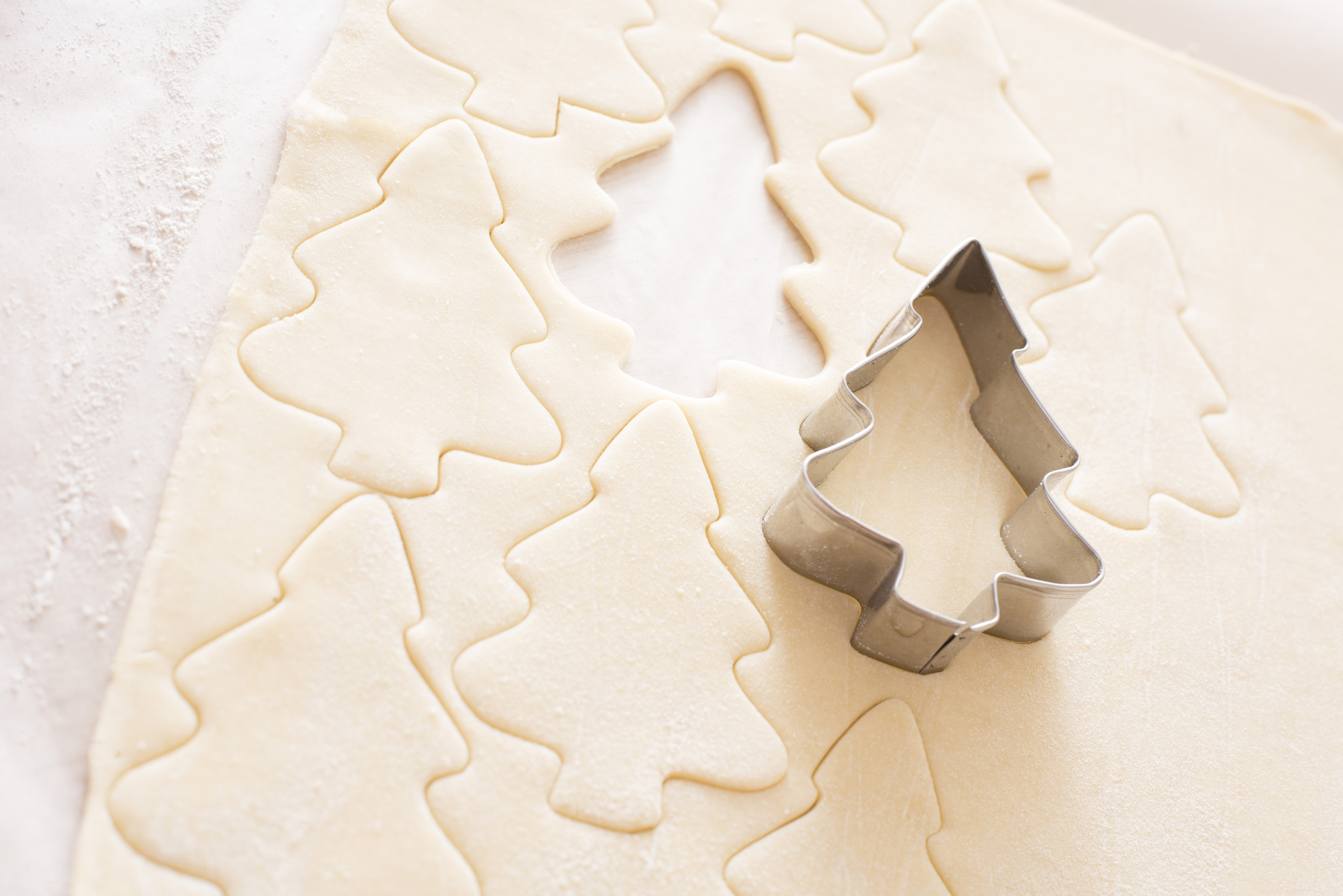 Baking traditional homemade Christmas cookies with rolled fresh dough and a tree shaped cookie cutter in a close up view