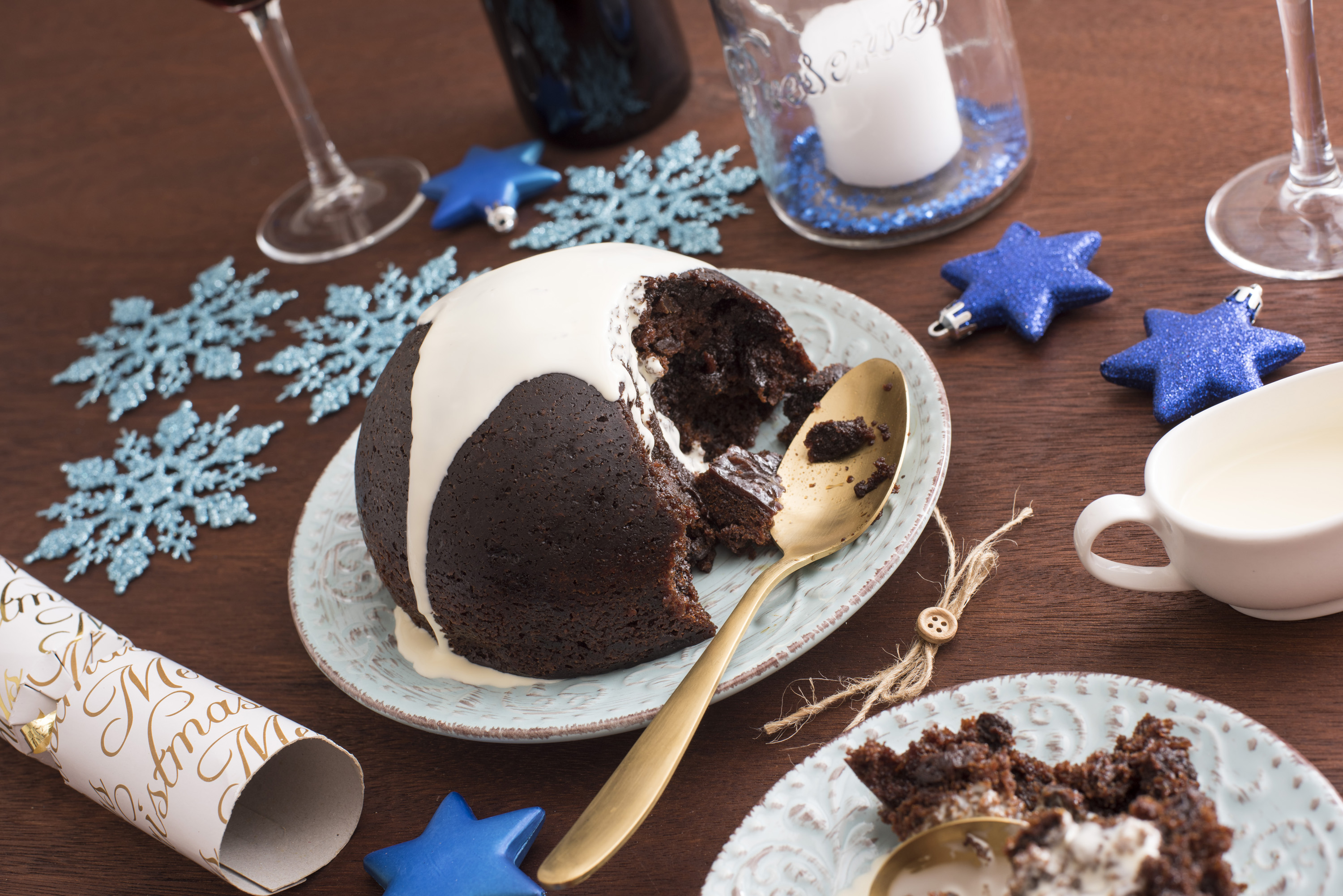 Delicious fruity Christmas pudding with brandy cream being served for dinner on a decorated table with blue snowflakes and stars