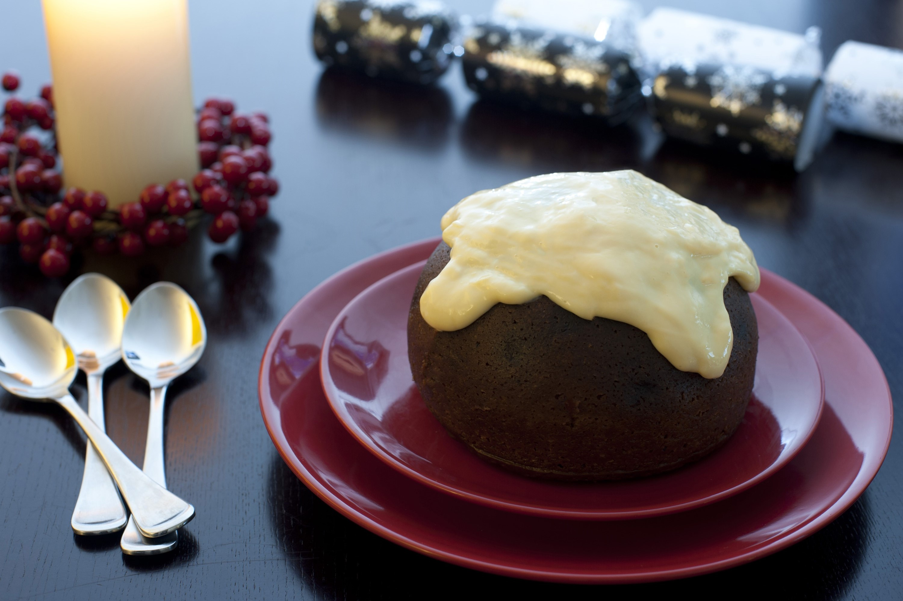 A small traditional steamed fruity Christmas pudding topped with brandy custard and served for dessert on a festive table