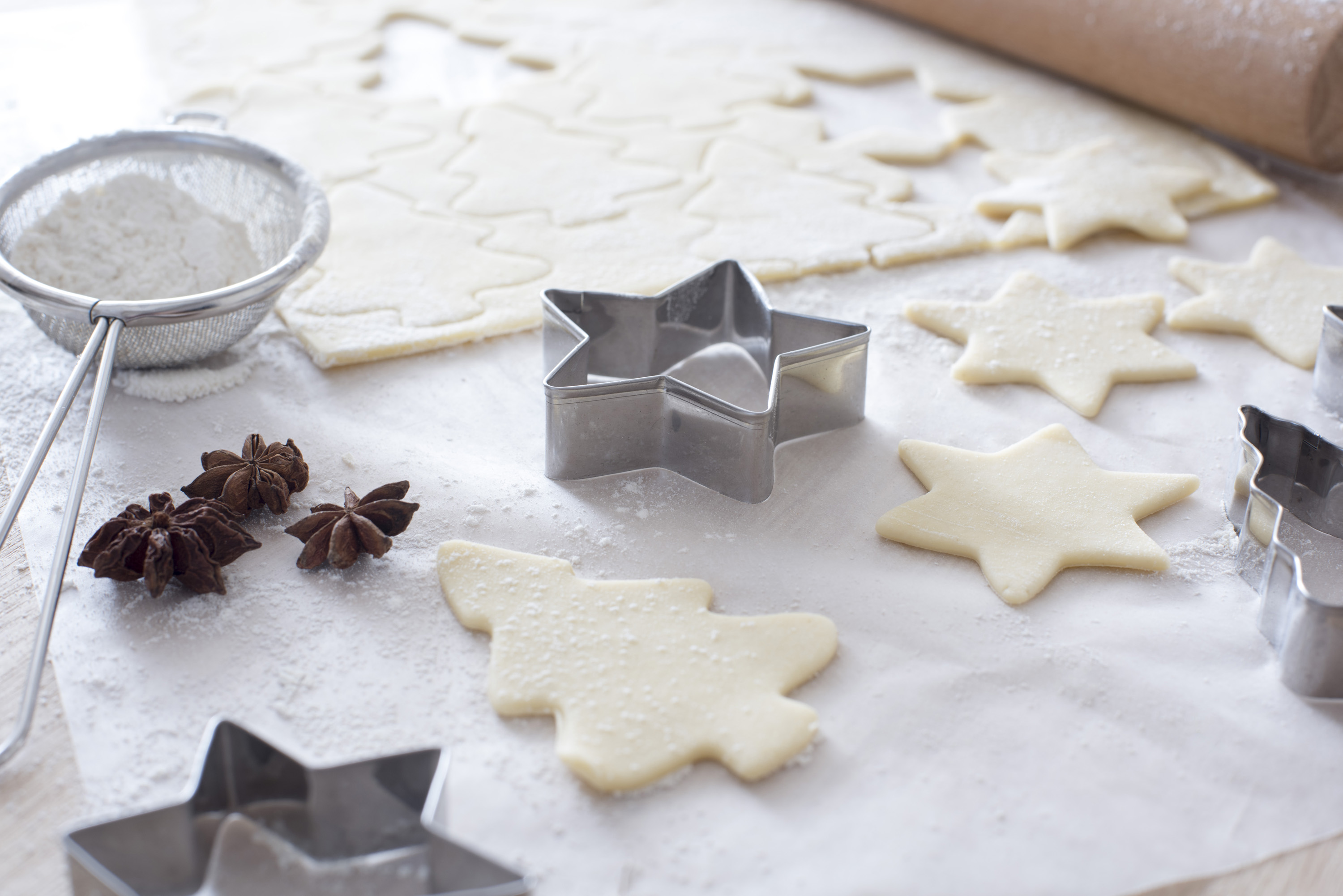 Work space for baking with cookie sheet, rolling pin and shaped cutters beside star anise