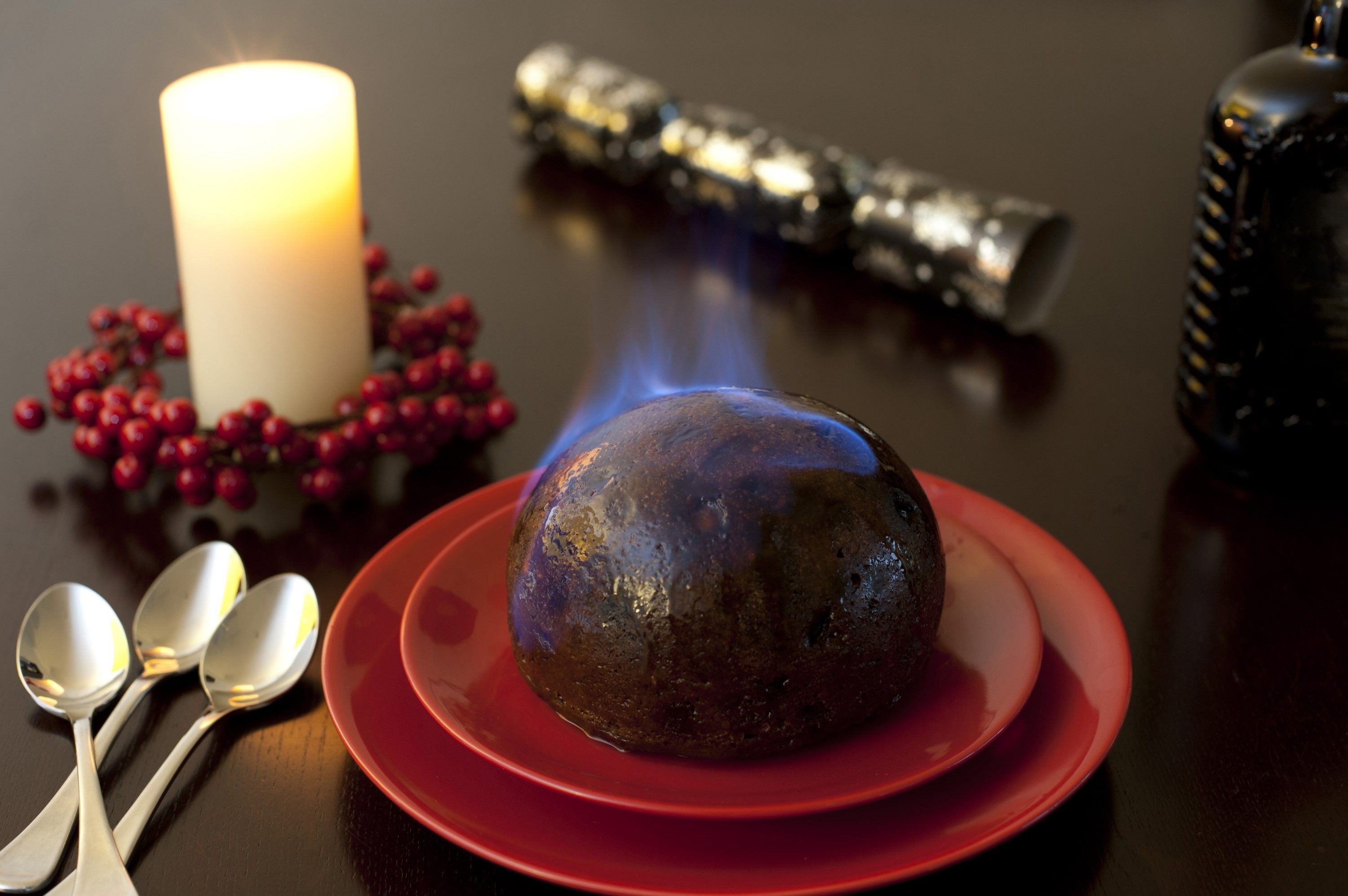 Traditional rich fruity flaming brandy pudding served for a delicious Christmas dessert on festive red plates standing on a table with a glowing seasonal candle