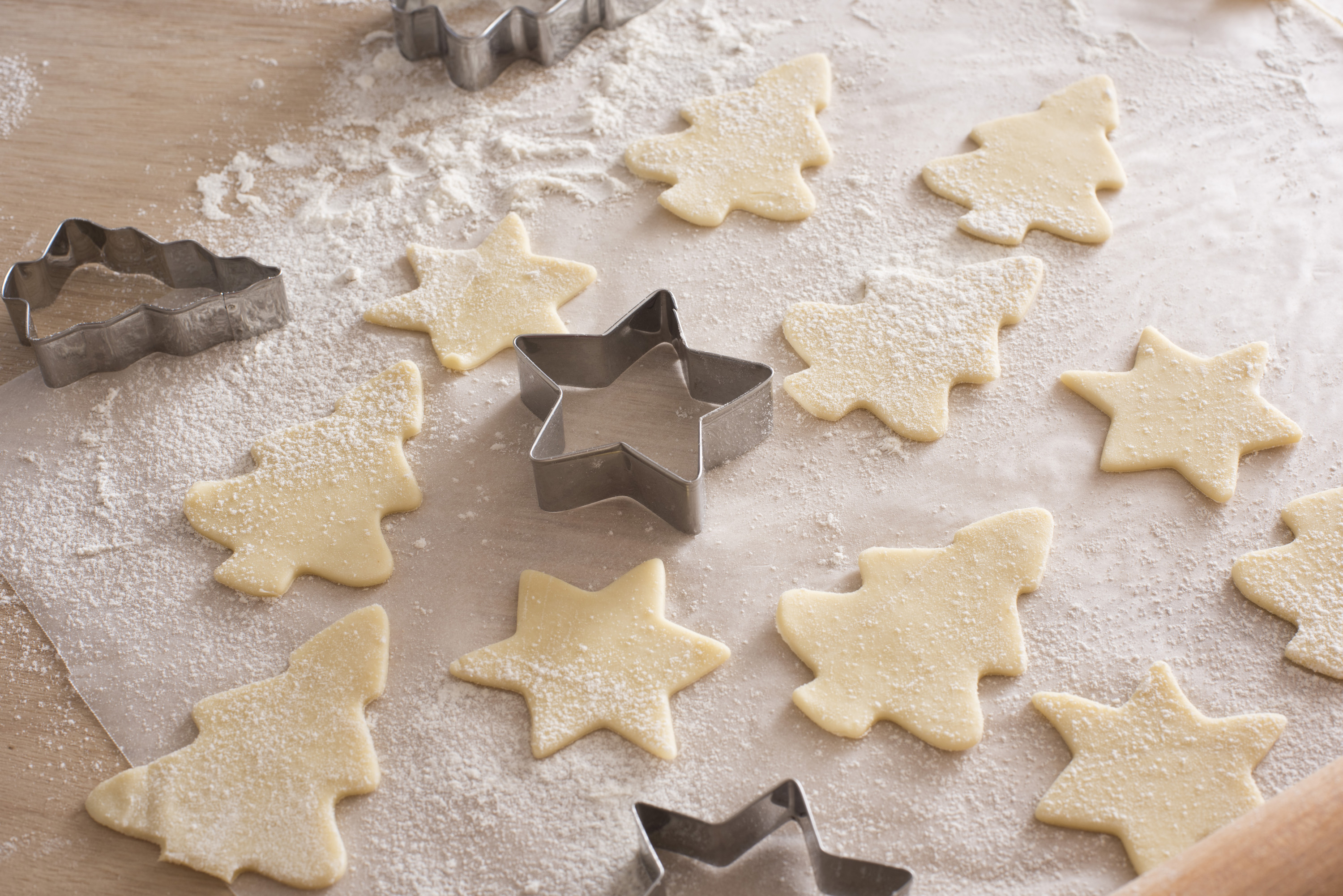 Baking festive tree and star christmas cookies with metal cookie cutters and uncooked pastry shapes on oven paper in a seasonal kitchen