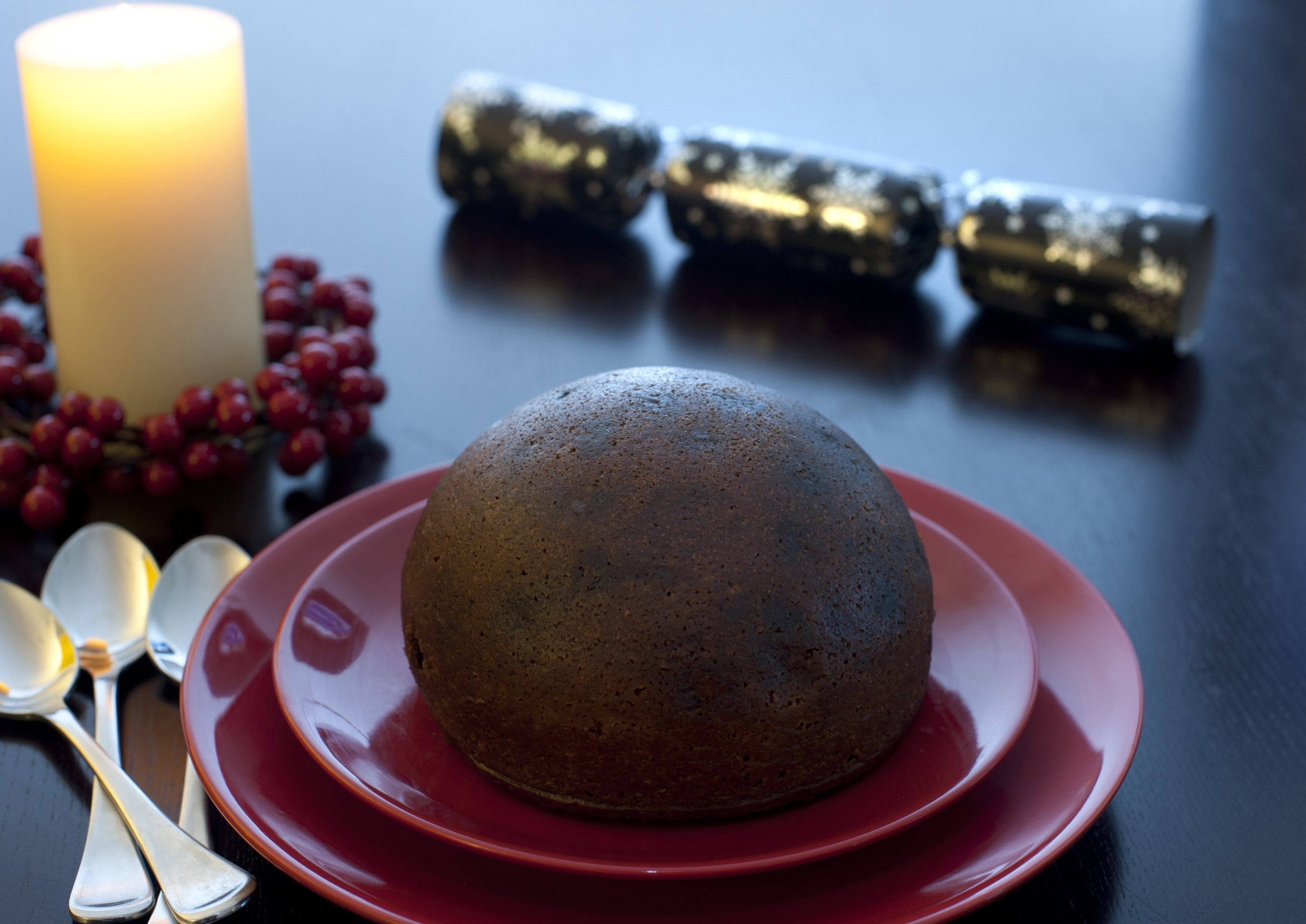 Large traditional steamed spiced Christmas fruit pudding served on festive red plates on the dinner table with a glowing candle and berry wreath to celebrate the Xmas season