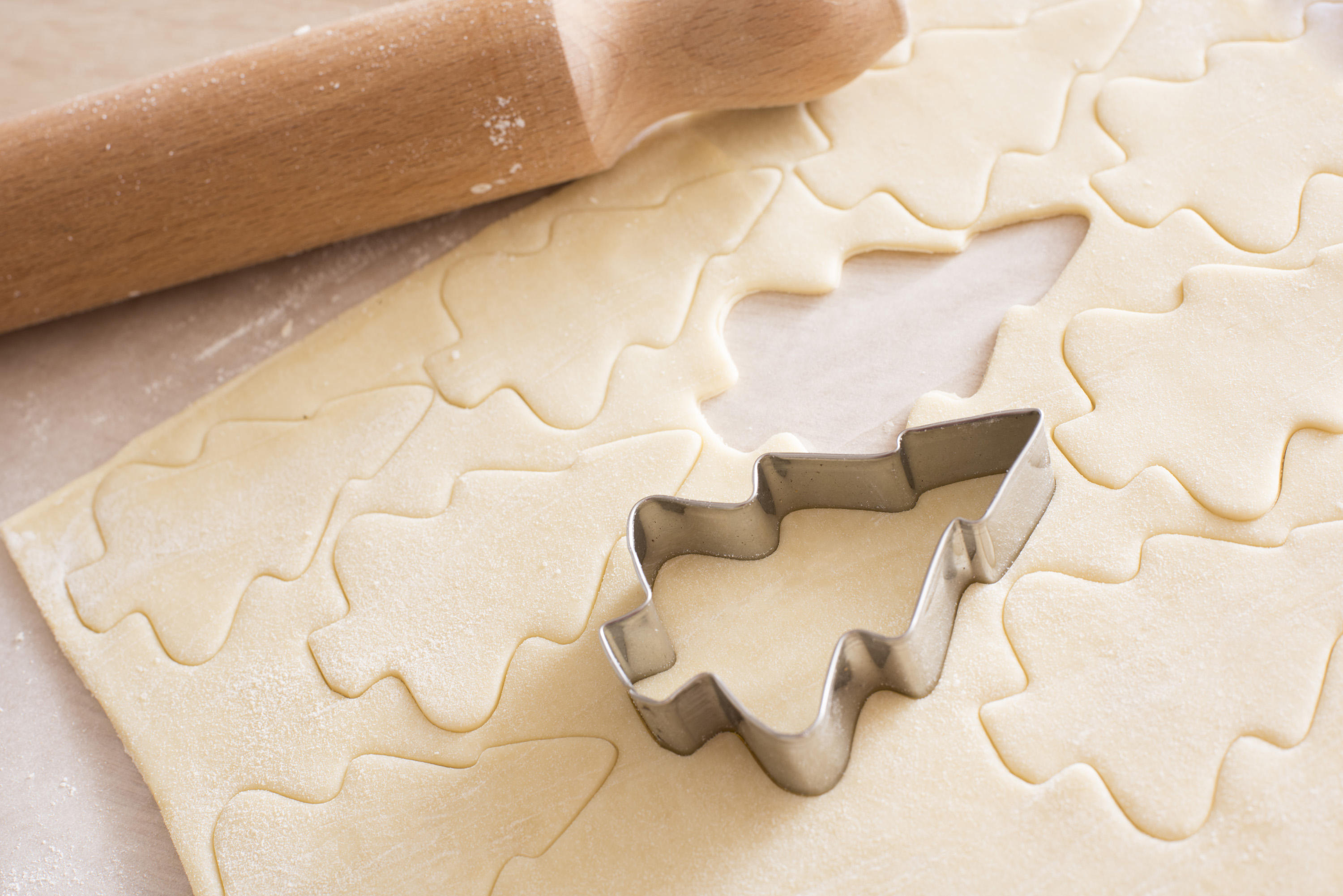 Making Christmas tree cookies in a home kitchen with rolled uncooked pastry with cut out shapes and a metal cookie cutter alongside a wooden rolling pin