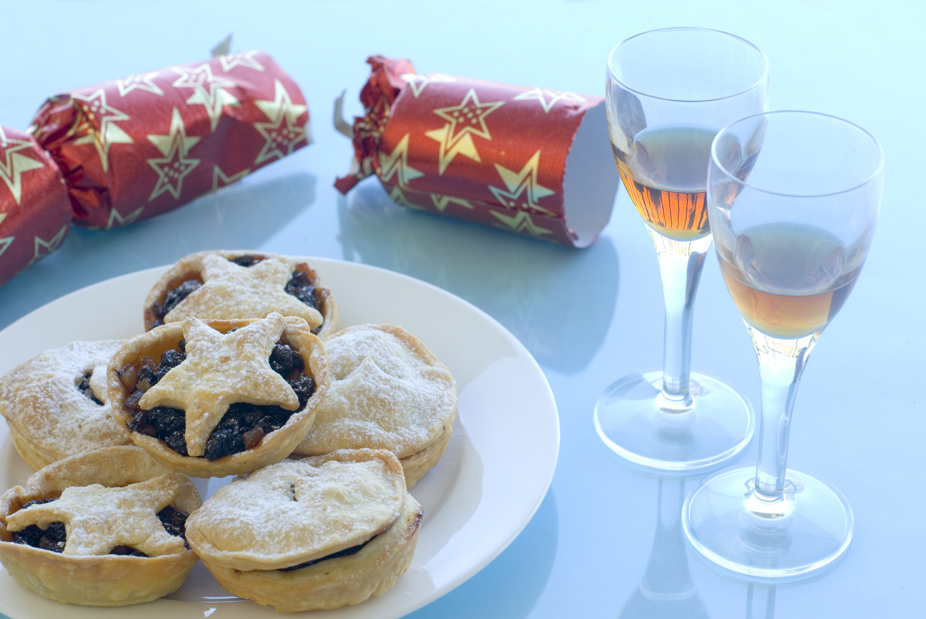 a plate of christmas mincemeat pies and glasses of sherry