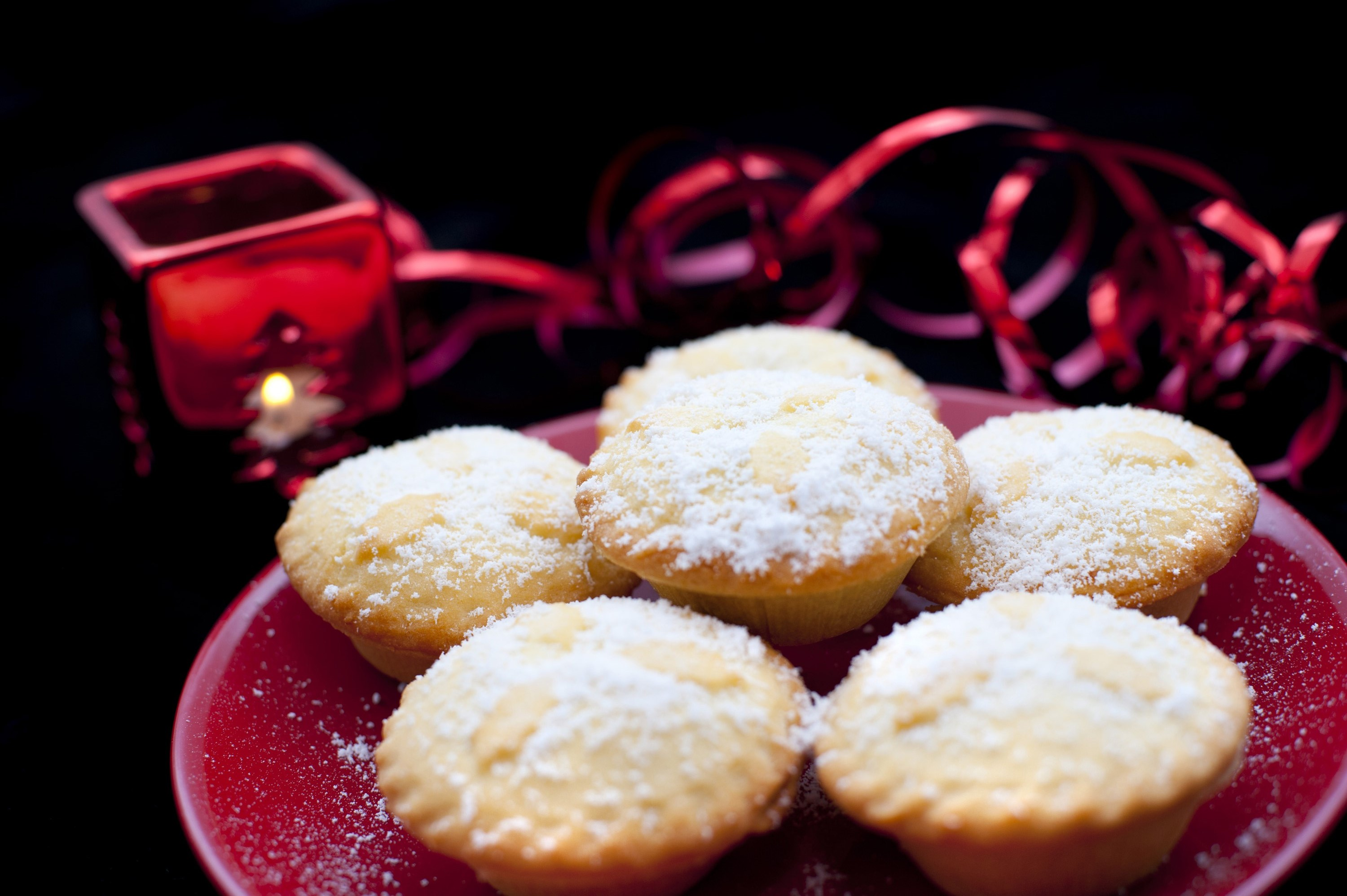 Plate of Christmas mince pies with golden crusts and fruity filling sprinkled with sugar and served on a red plate on a festive table with decorations