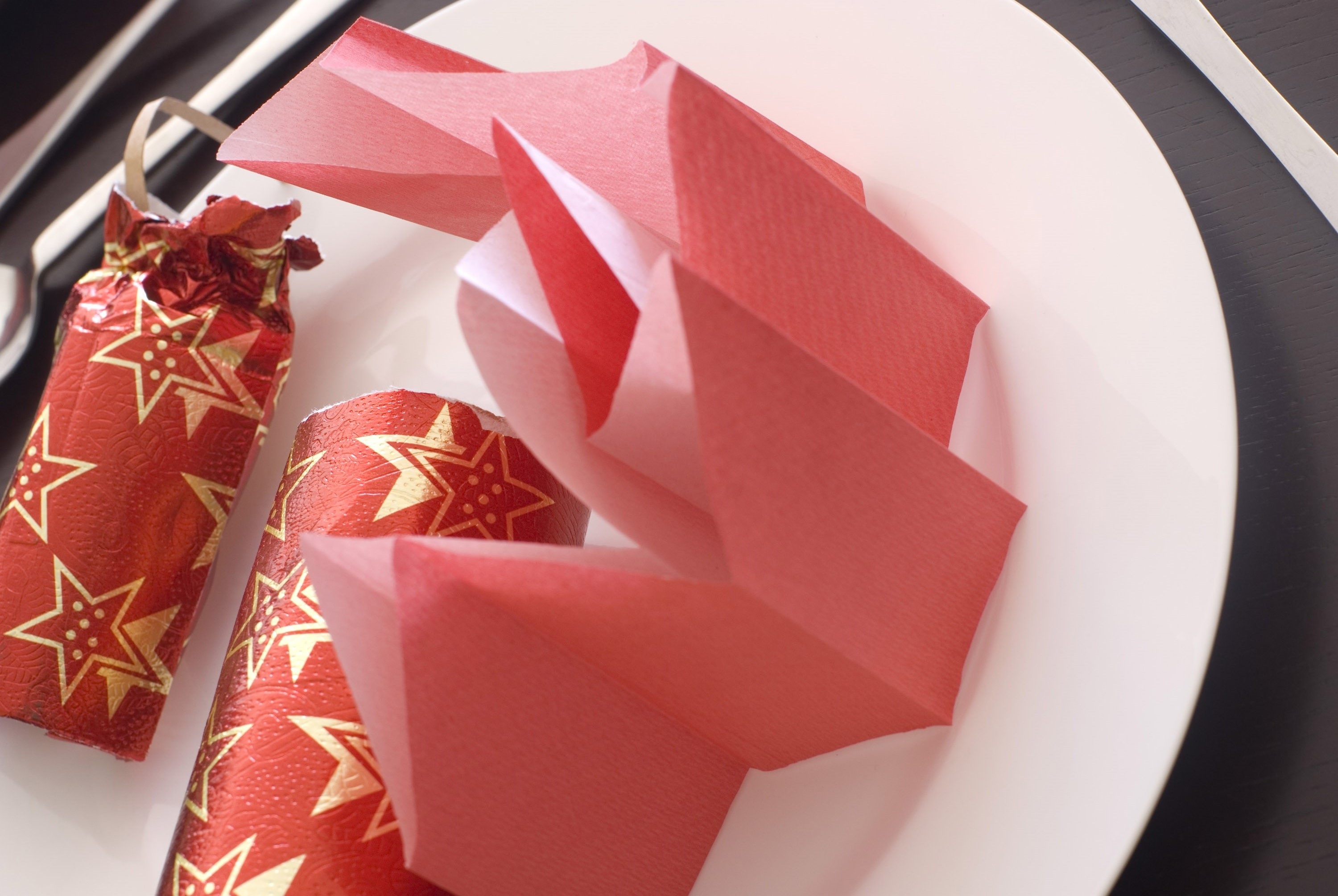 a pulled red christmas cracker and paper party hat
