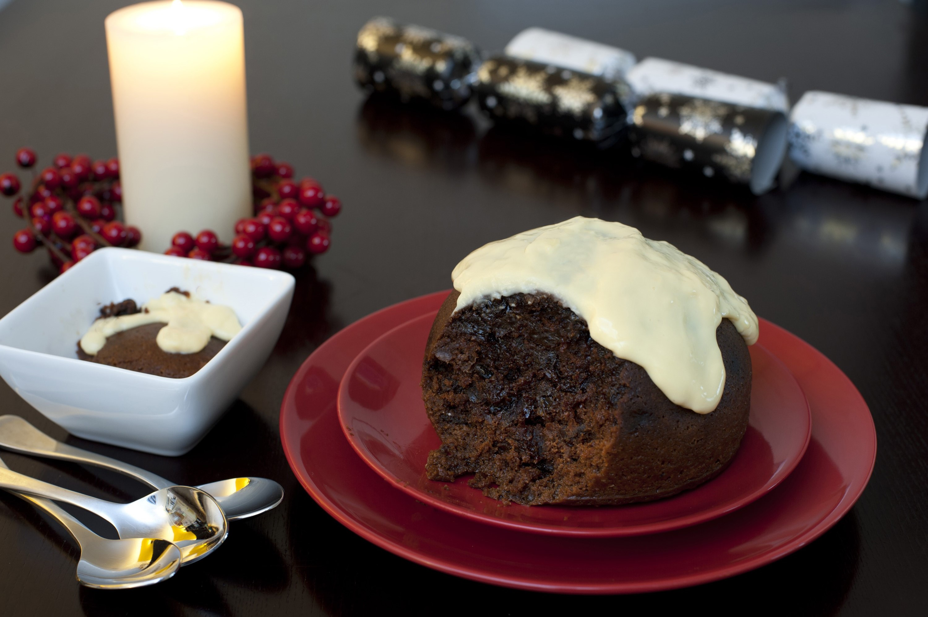 Delicious traditional Christmas pudding with a rich fruity texture topped with brandy sauce and served on a festive Christmas table