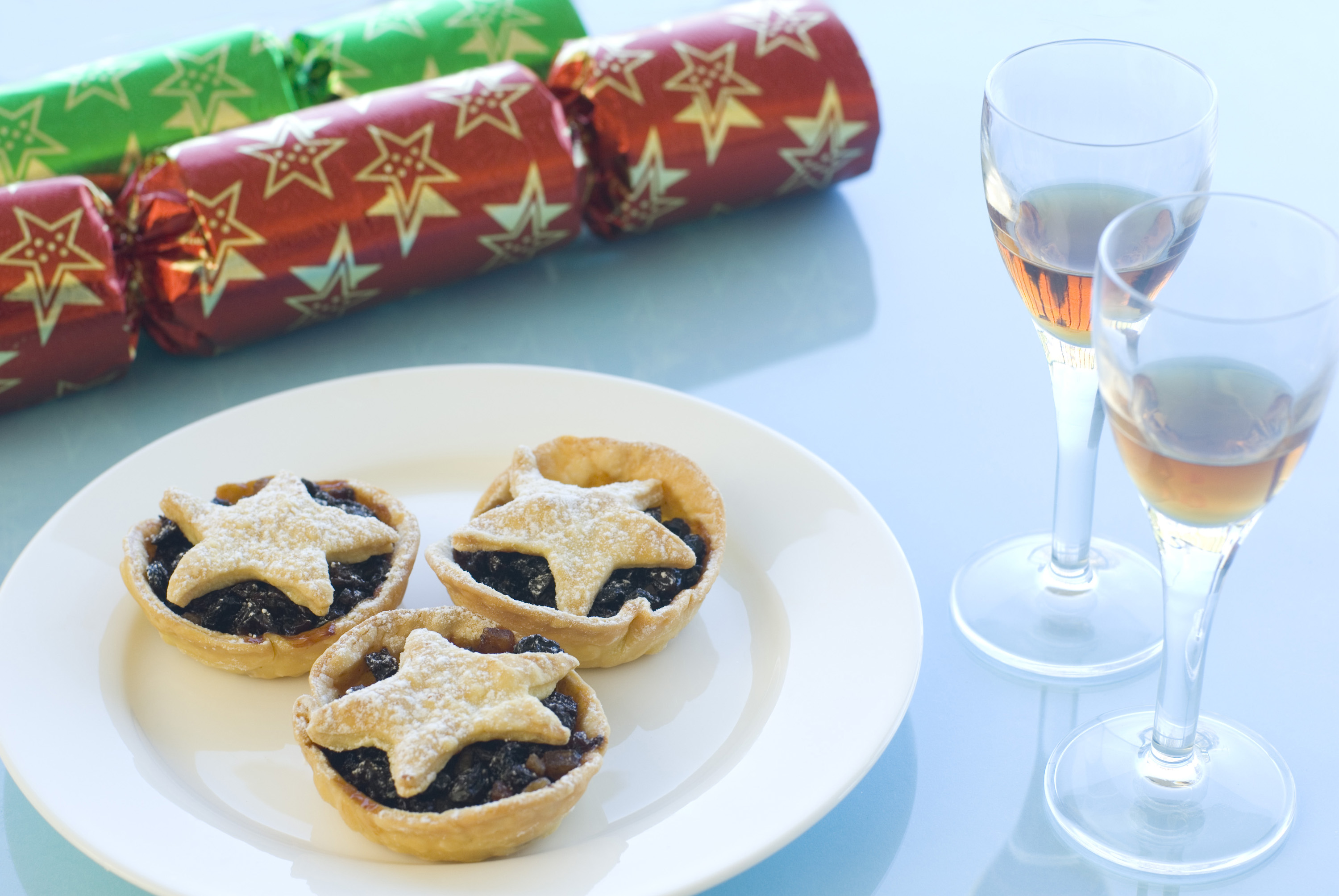 a plate of christmas mince pies with star shaped pastry tops