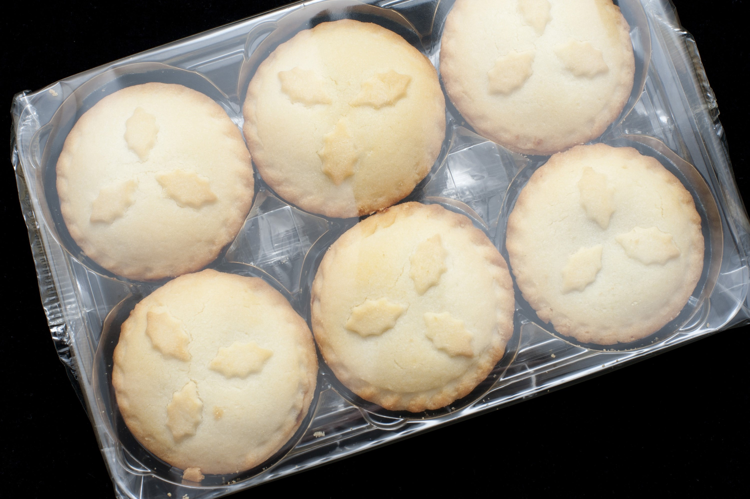 Festive fruity Christmas mince pies in their plastic packaging from the supermarket for a festive seasonal treat, overhead view