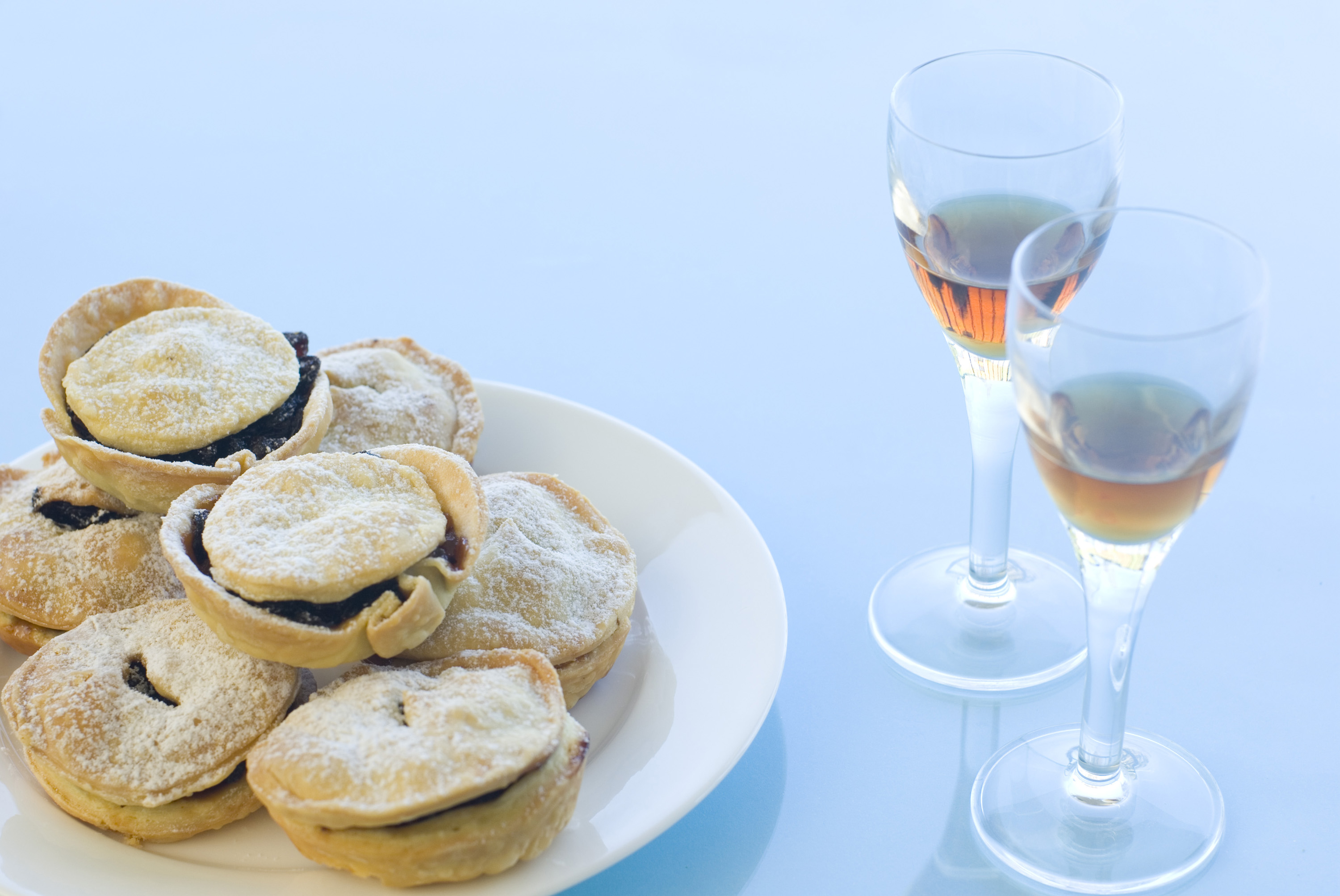 a plate of christmas mince pies and glasses of sherry - traditional british christmas treat