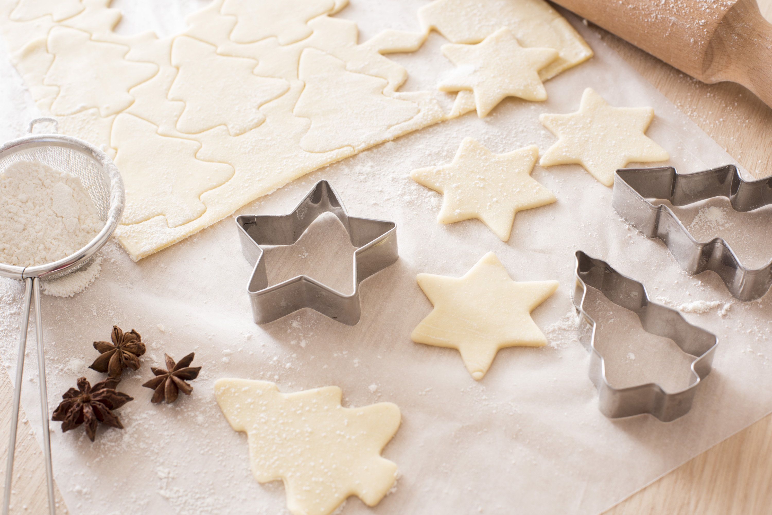 Baking traditional spicy Christmas cookies with star anise and cut out uncooked pastry tree and star shapes alongside seasonal metal cutters on oven paper on a wooden kitchen counter
