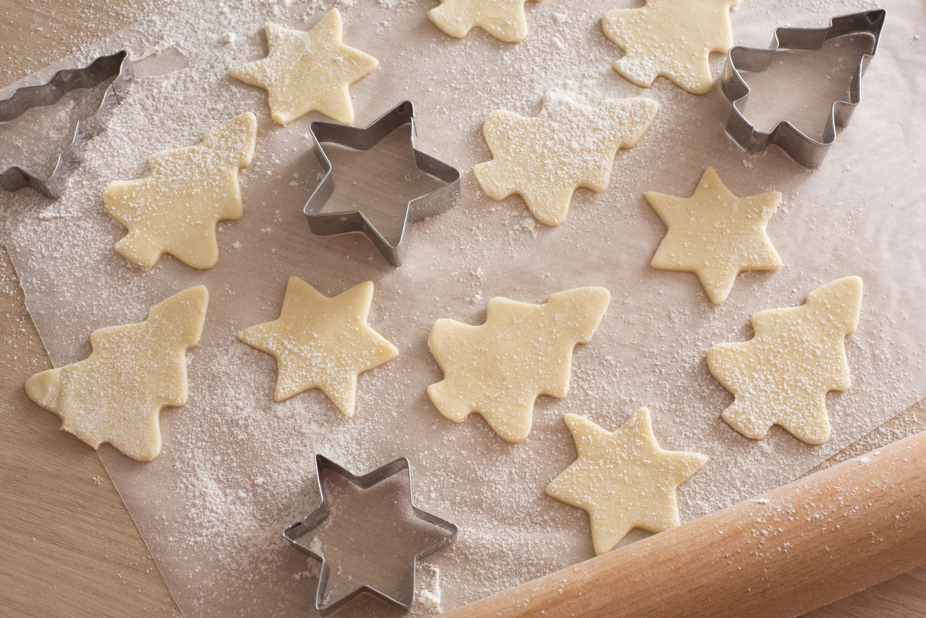 Making traditional Christmas cookies at home with star and tree shaped cookie cutters alongside cut out uncooked dough on floured paper on the kitchen counter