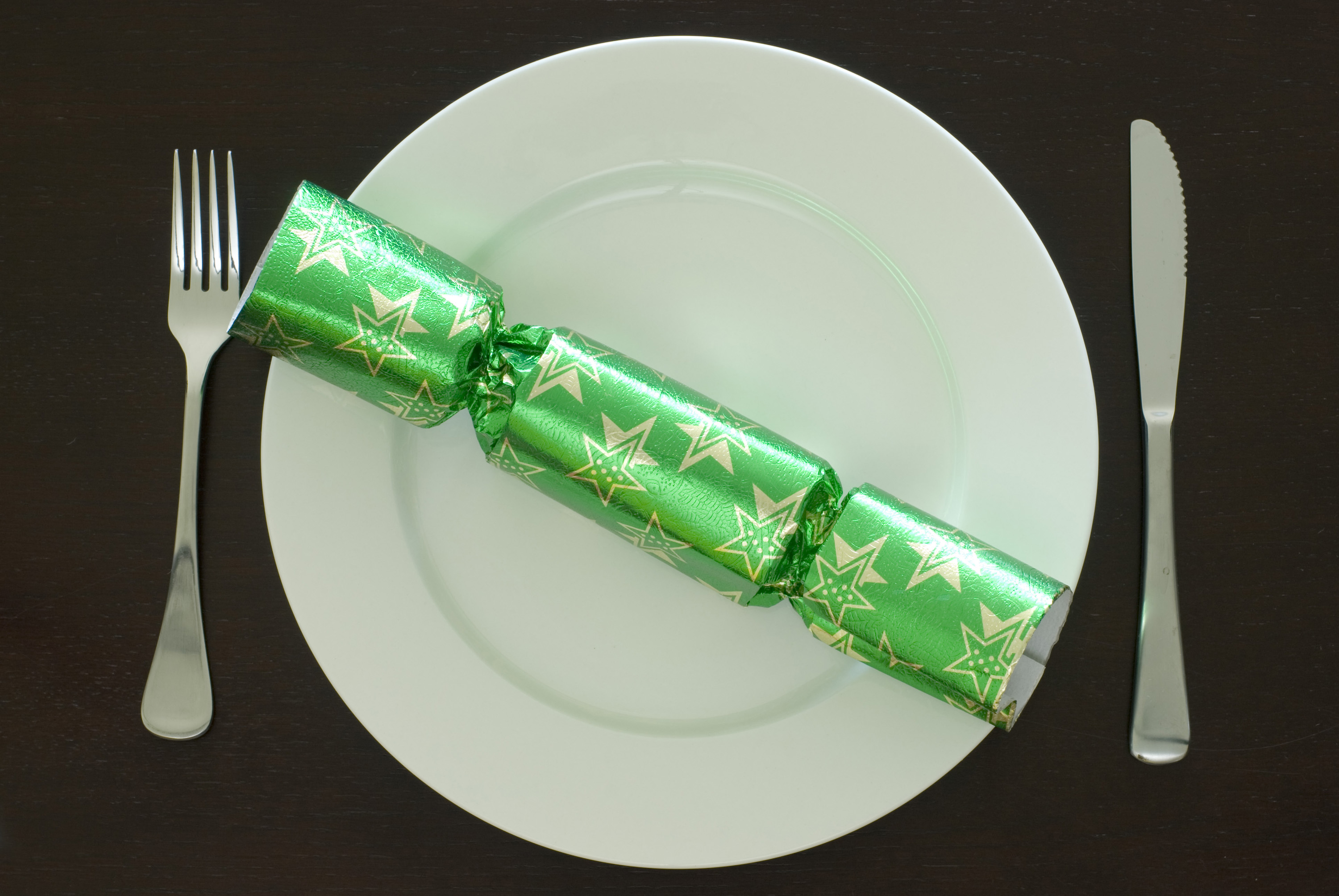 a plate set at a christmas dinner table, knife, fork and a festive cracker