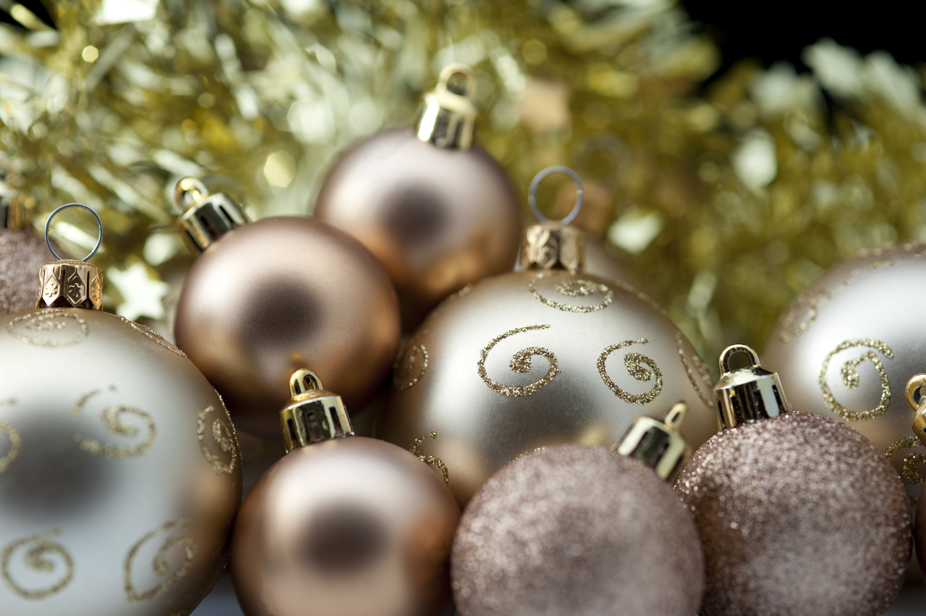 Golden Christmas baubles of various sizes and textures with focus to one with glitter curlicues, copyspace at the top