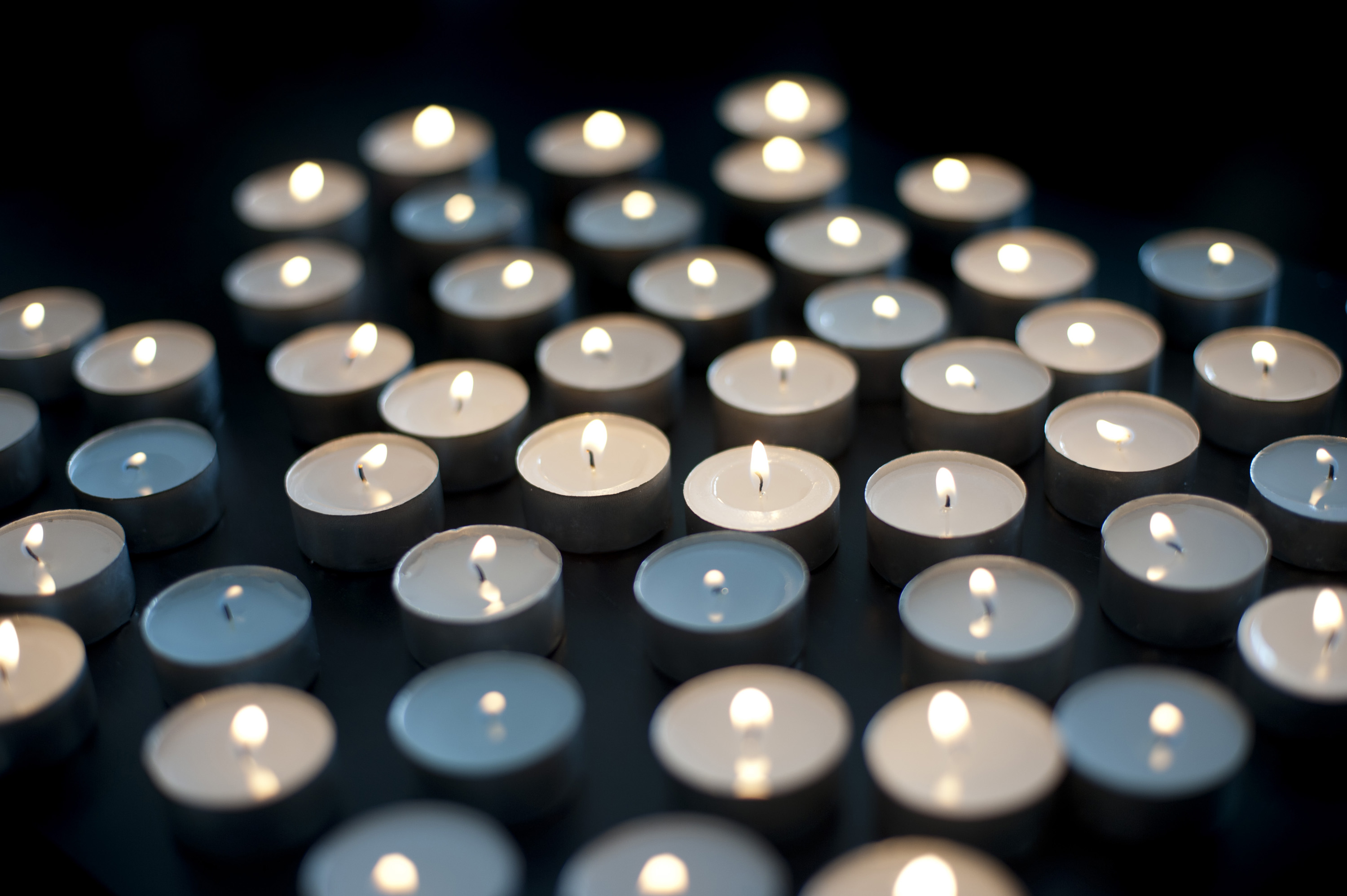 Array of small round burning candles celebrating the Christmas faith against a dark background