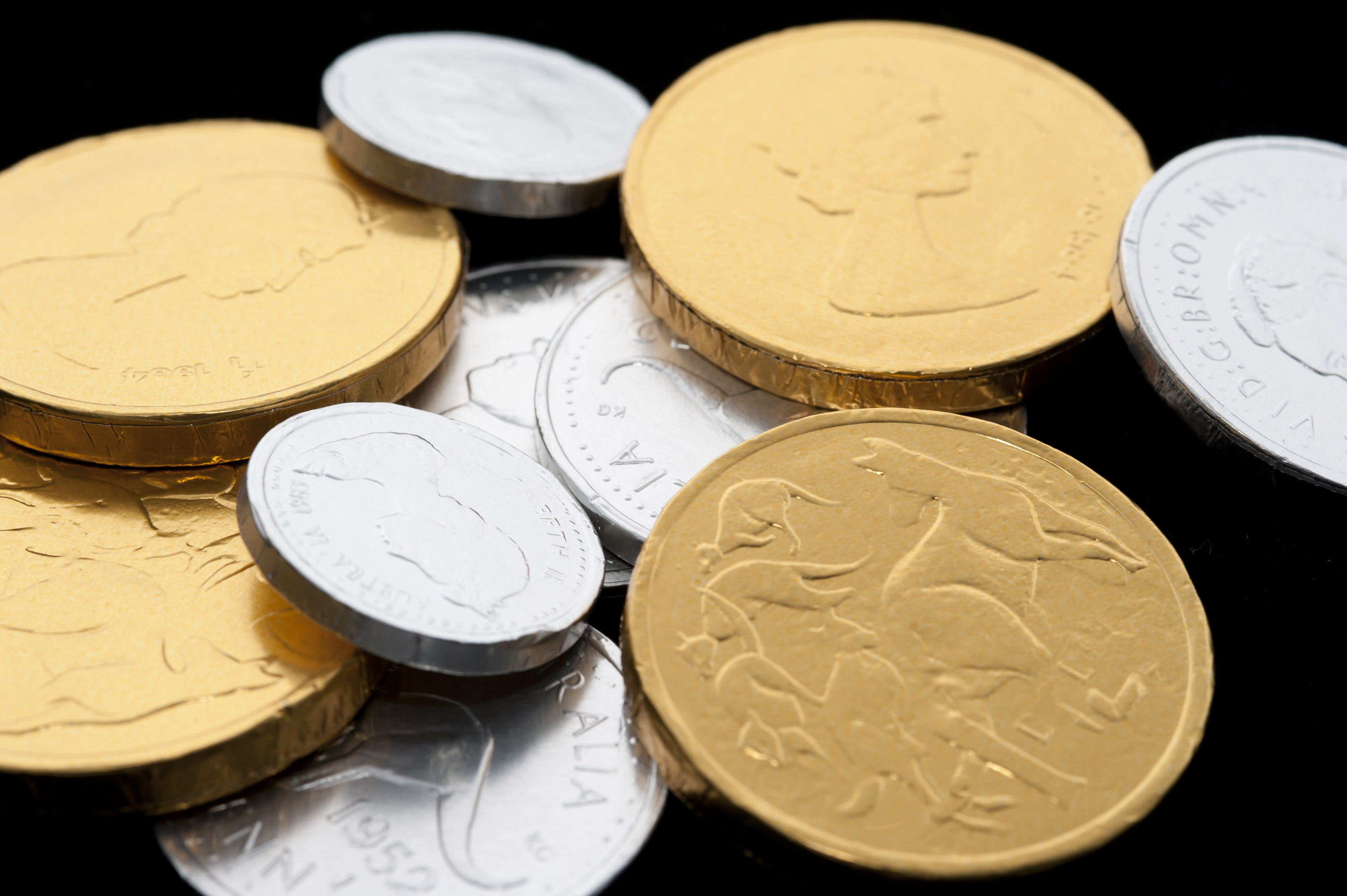 Festive gold and silver foil wrapped chocolate candy coins for a party celebration or for use in a display to represent wealth and riches