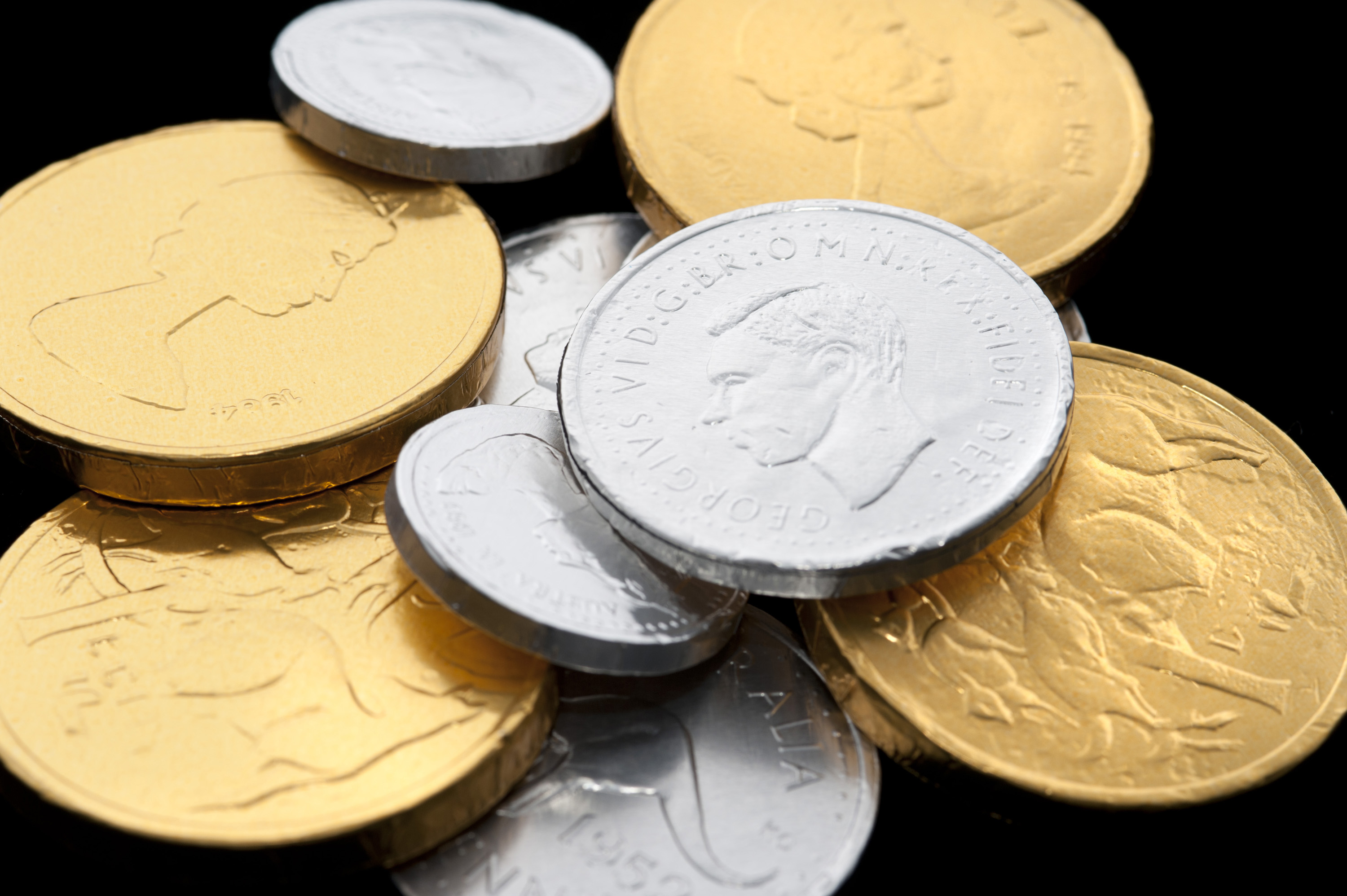 Close-up of chocolate coins wrapped in golden and silver shiny paper on black background