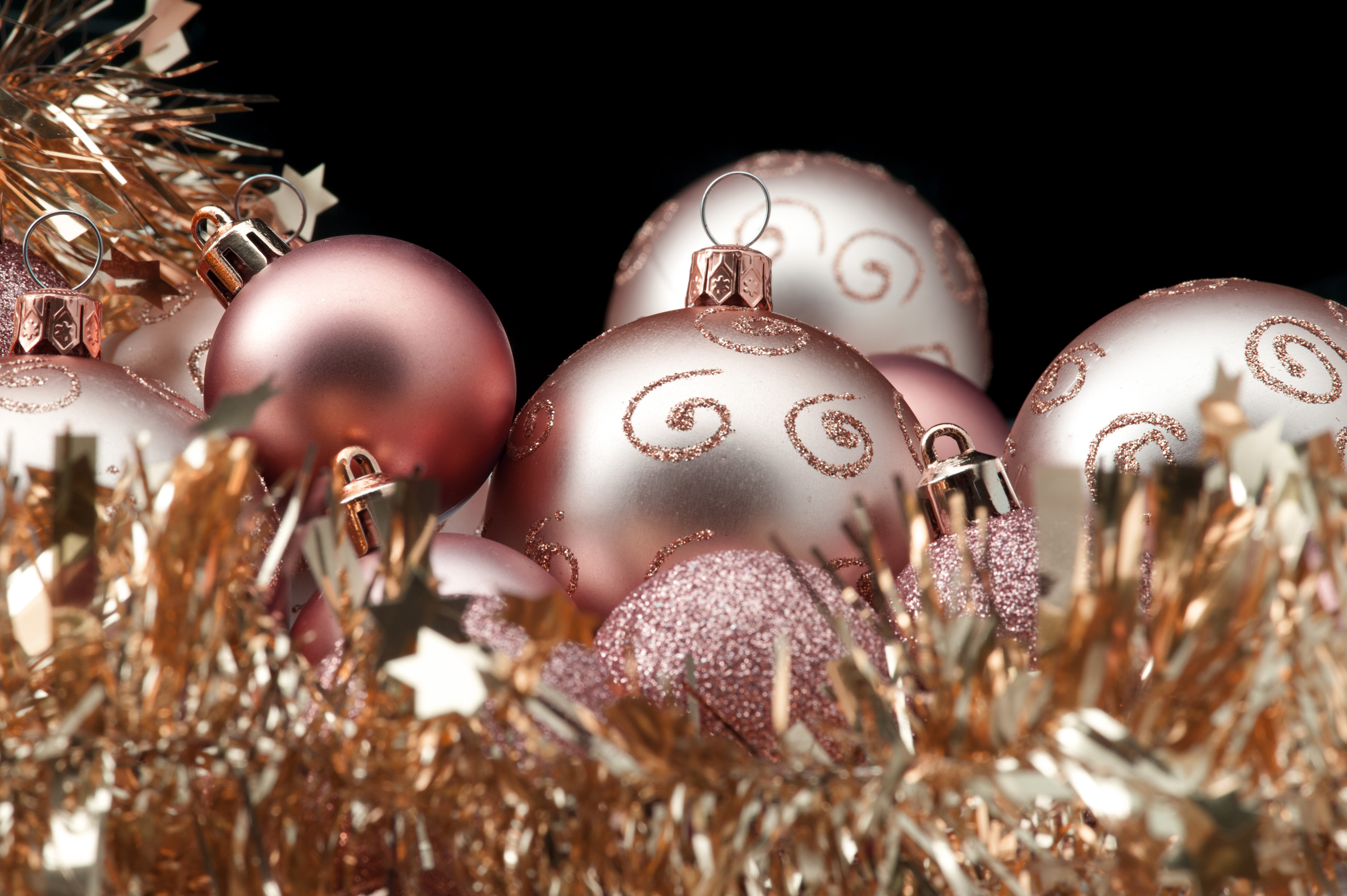 a background image with golden copper coloured christmas baubles and tinsel