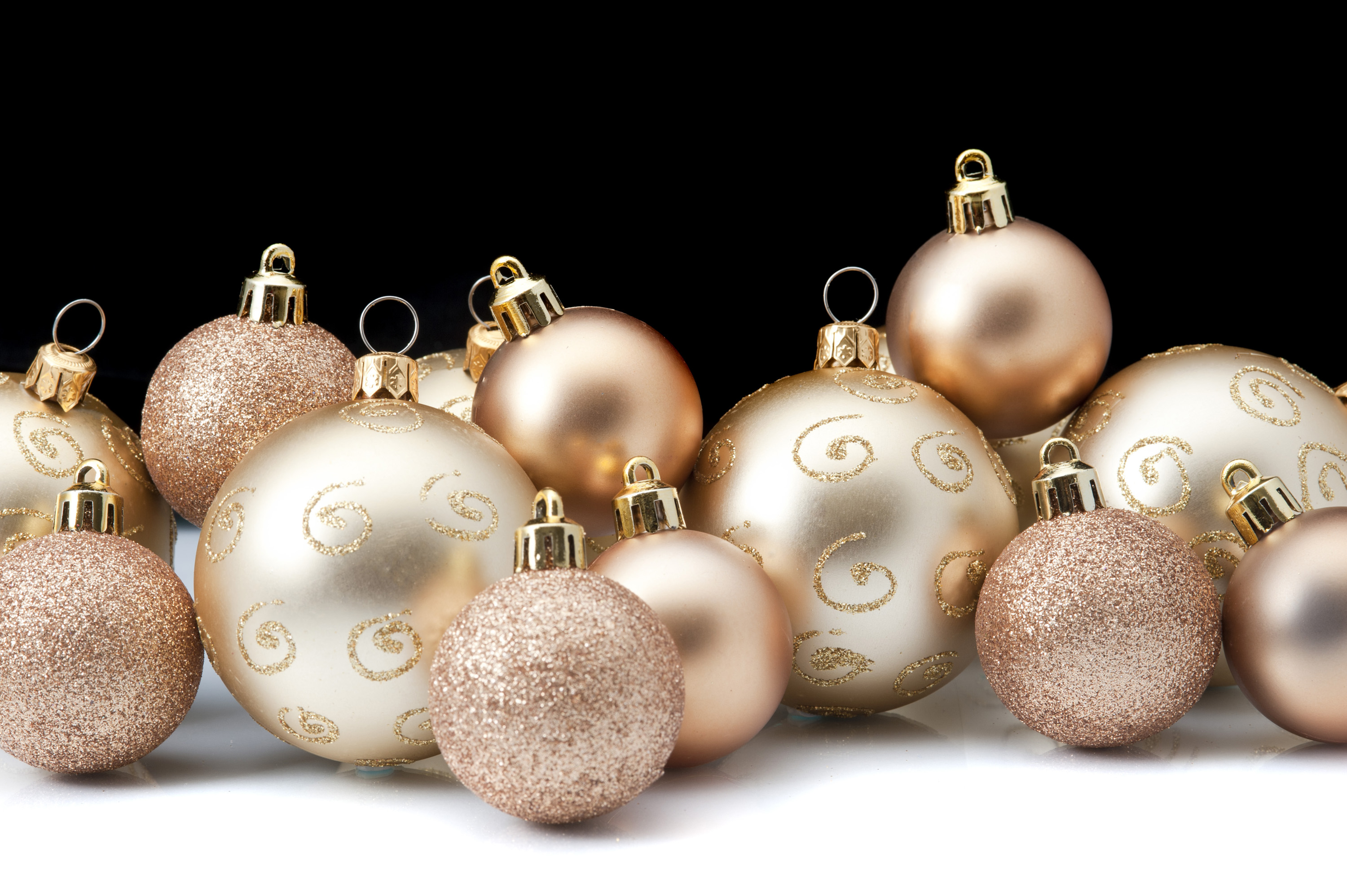 an arrangement of gold coloured christmas baubles with a back background and white foreground