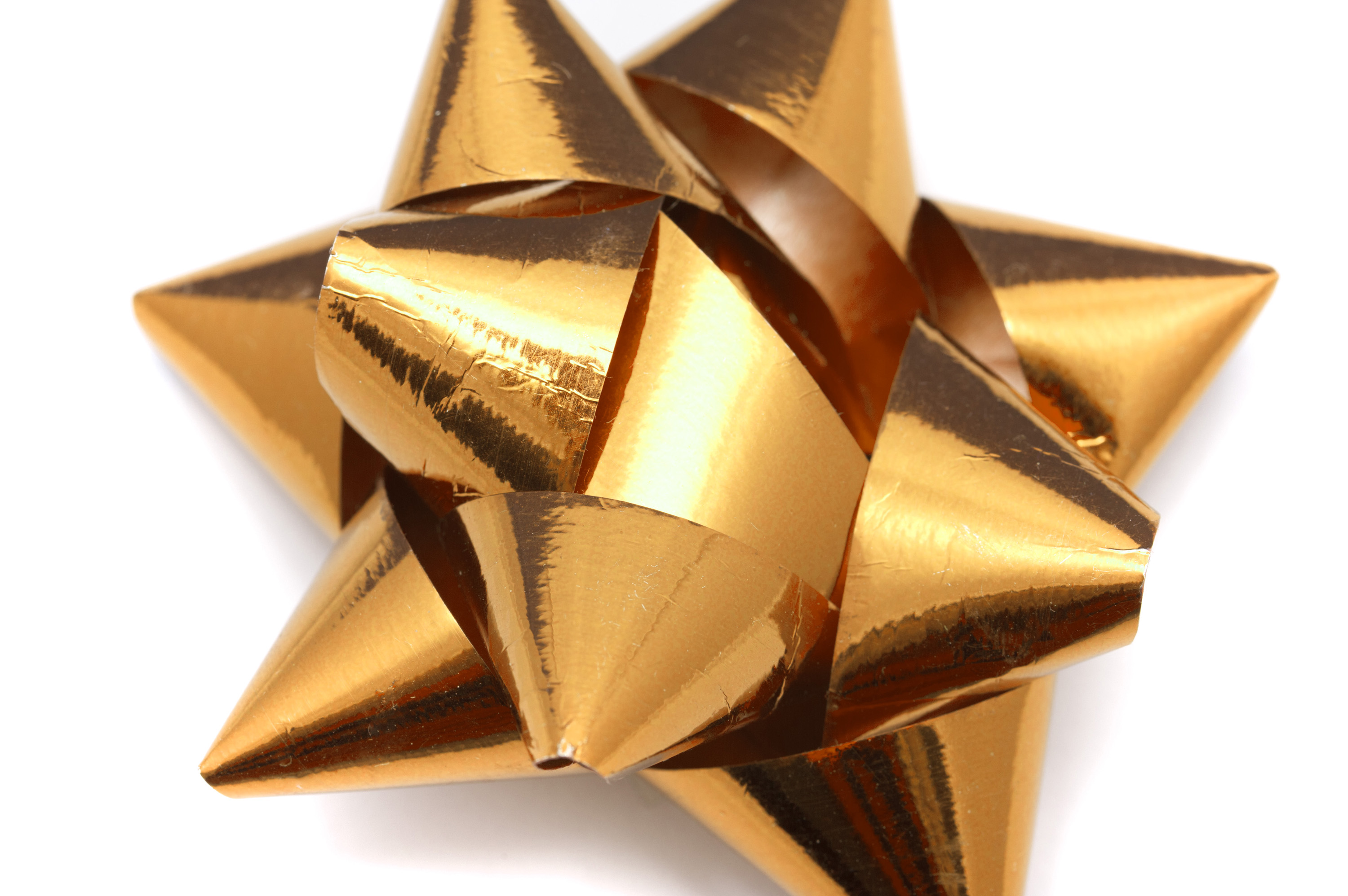 Shiny metallic golden foil ribbon bow for decorating festive gifts in a close up view on white