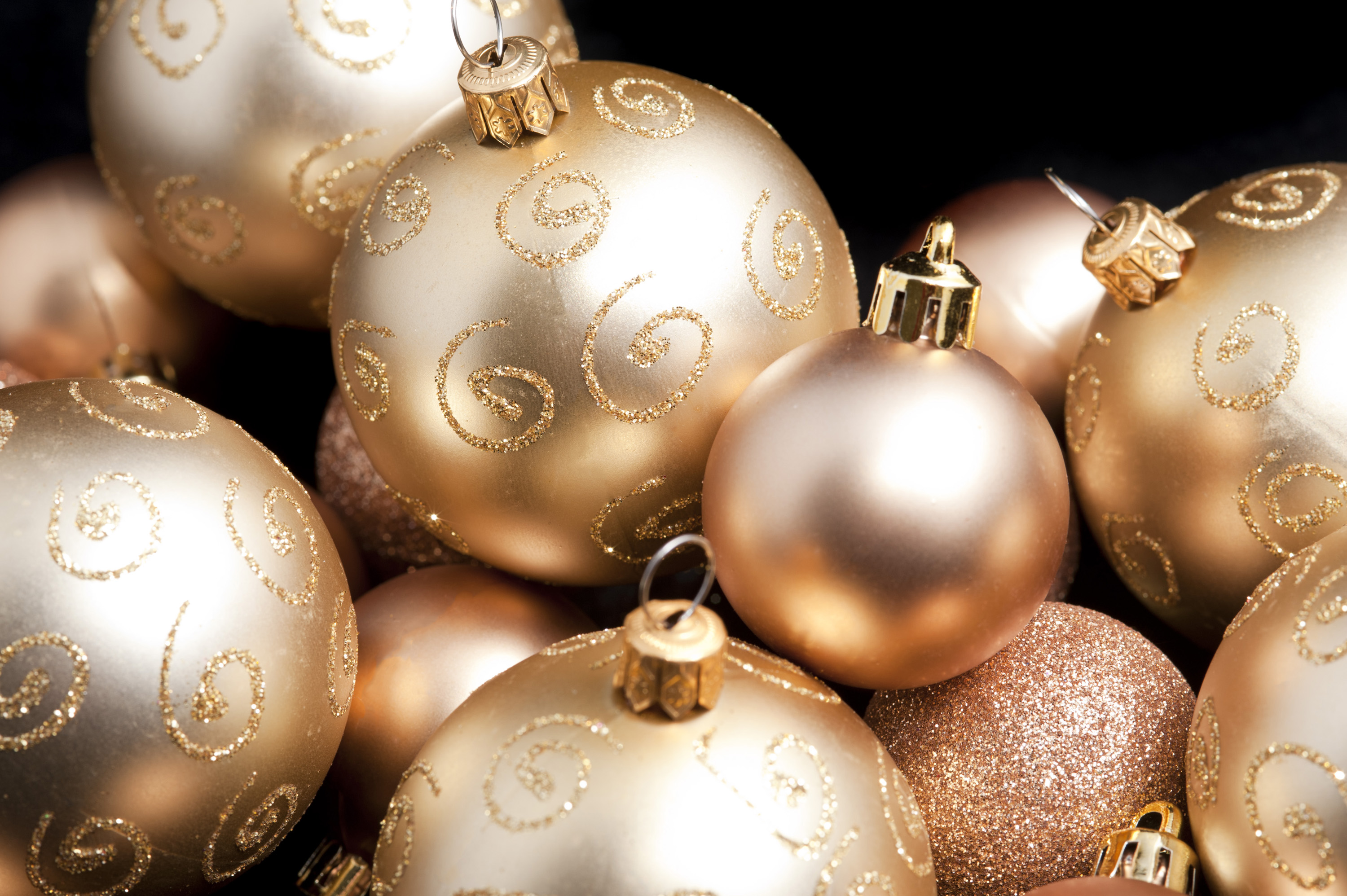 Festive background with random golden Christmas balls of different sizes, textures and patterns on a dark background