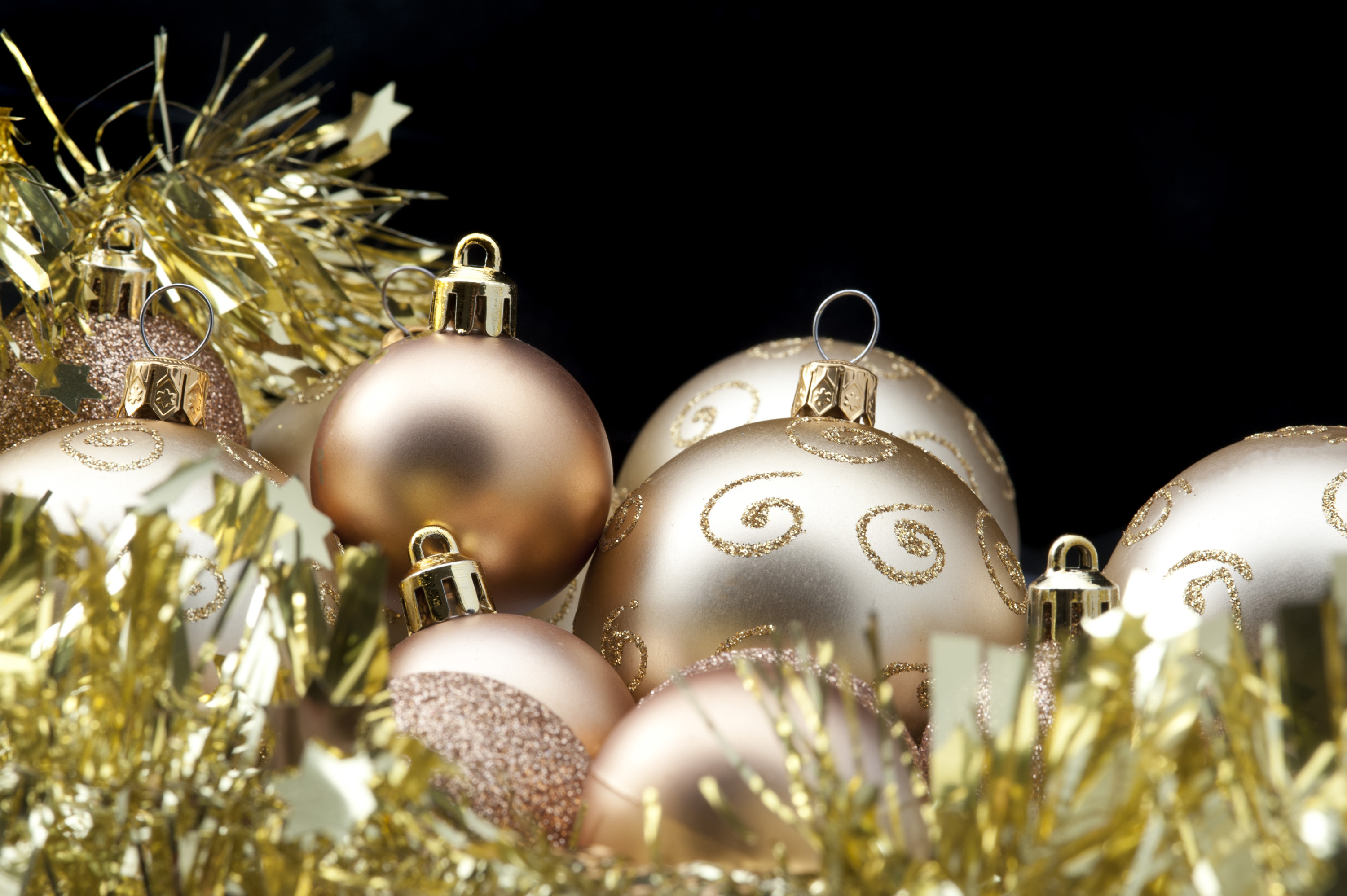 decorative background with gold coloured baubles and tinsel garland, space for text in the upper right