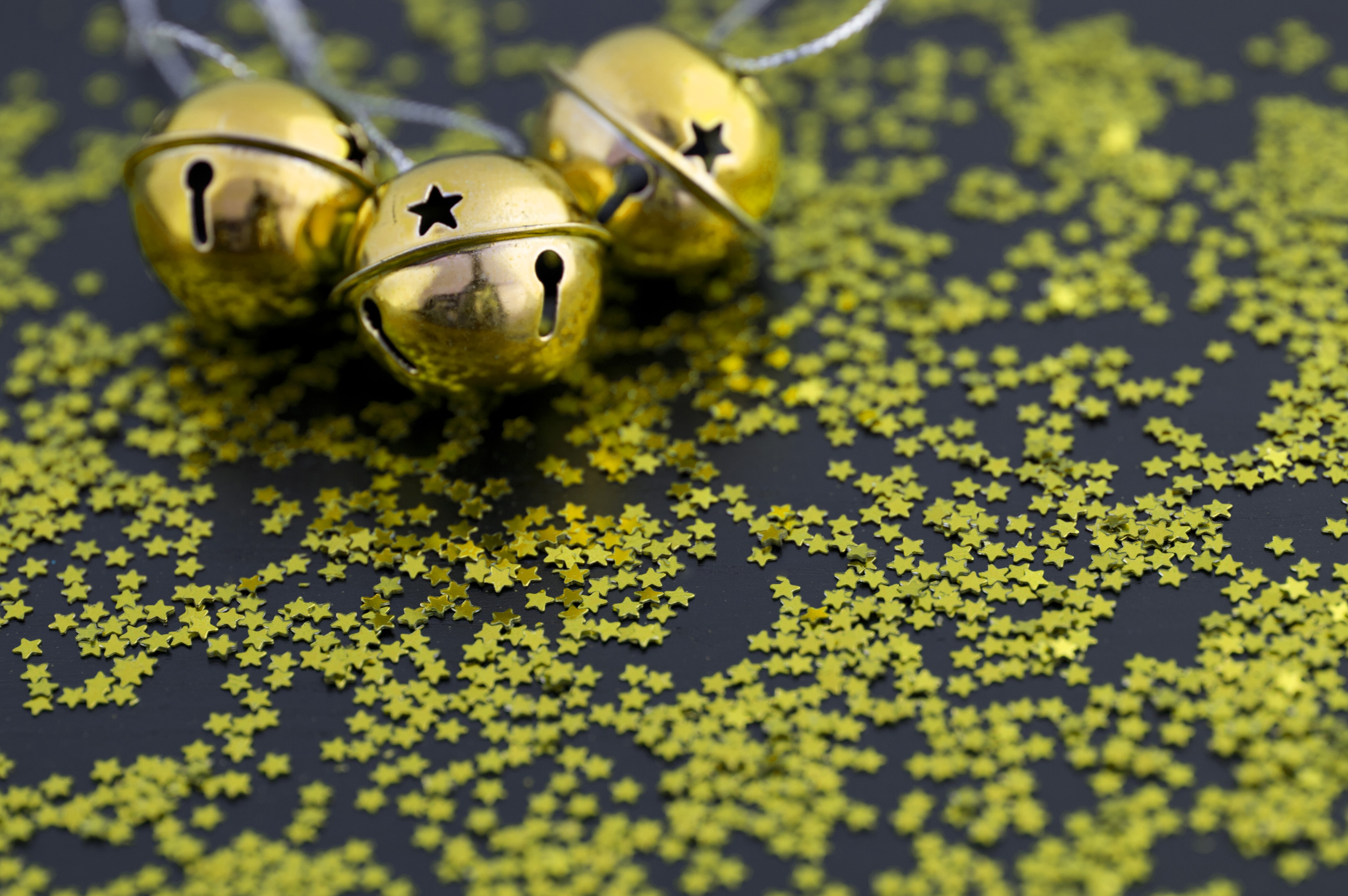 Golden Christams sleigh bells surrounded by scattered gold stars forming a copyspace for your seasonal greetings