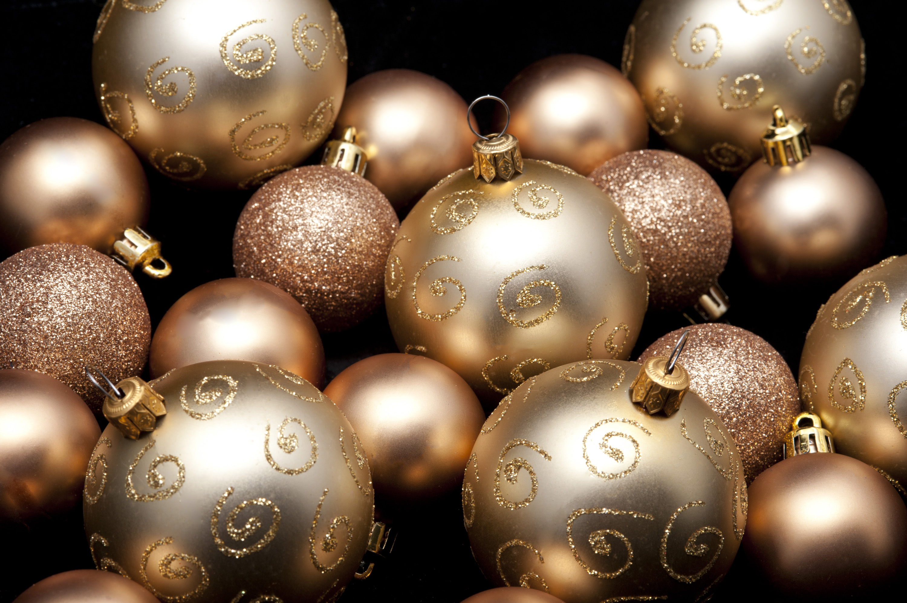 a selection of gold coloured christmas baubles of various sizes on a back background