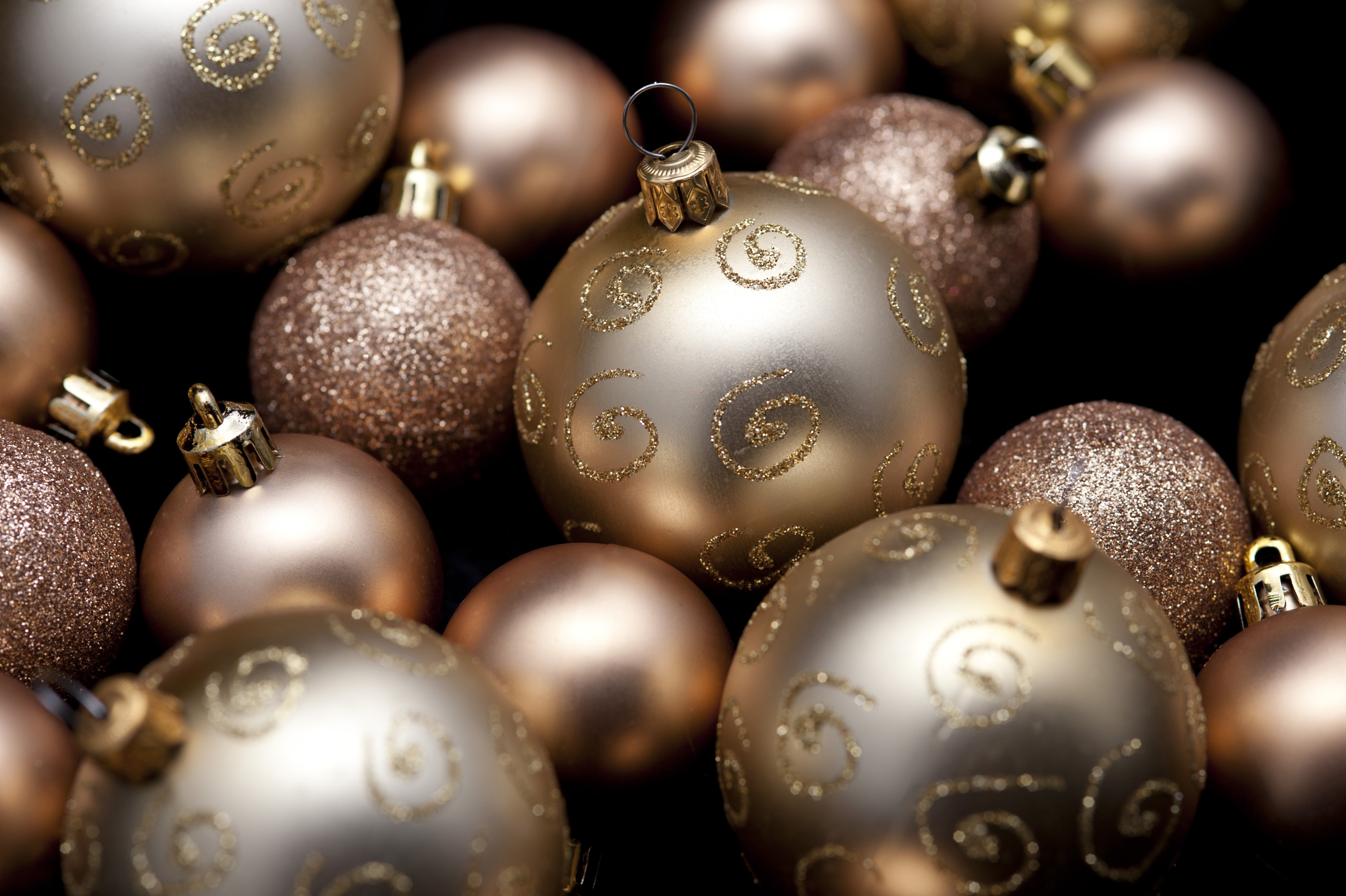 an random assortment of various types of gold coloured christmas baubles on a black background