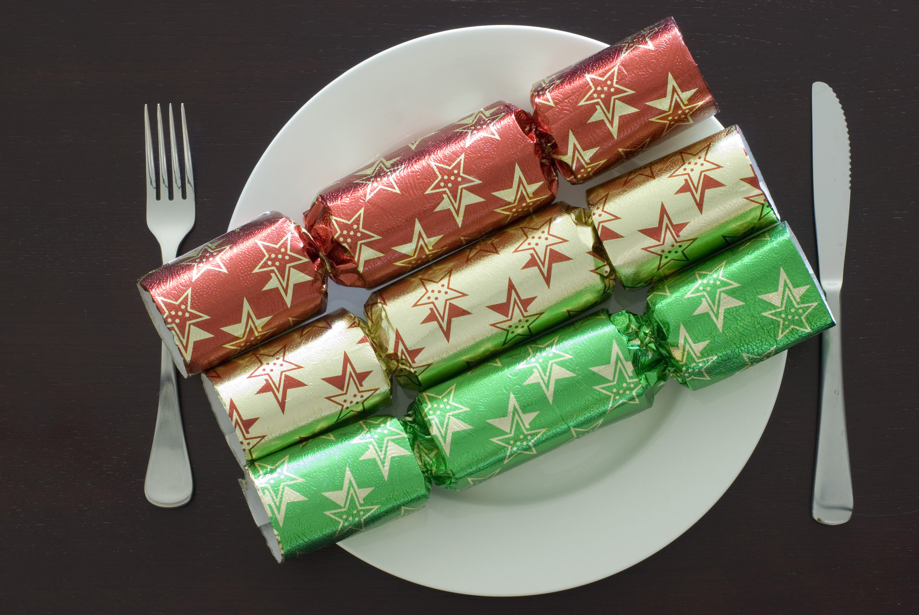 A christmas place setting with three different coloured crackers