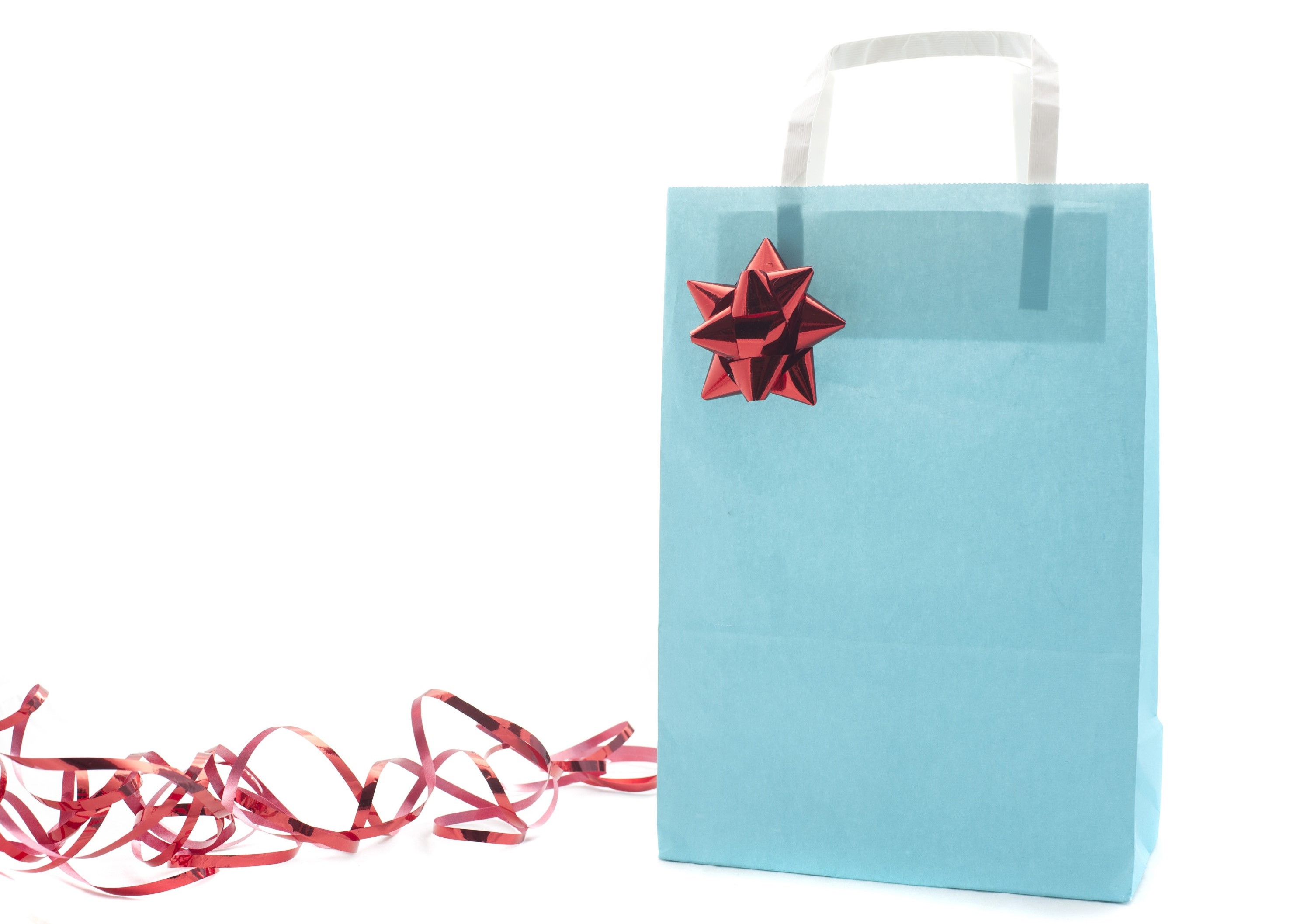 Pale blue paper Christmas gift bag decorated with a red foil bow and ribbon with a blank side for your greeting or copyspace alongside isolated on white