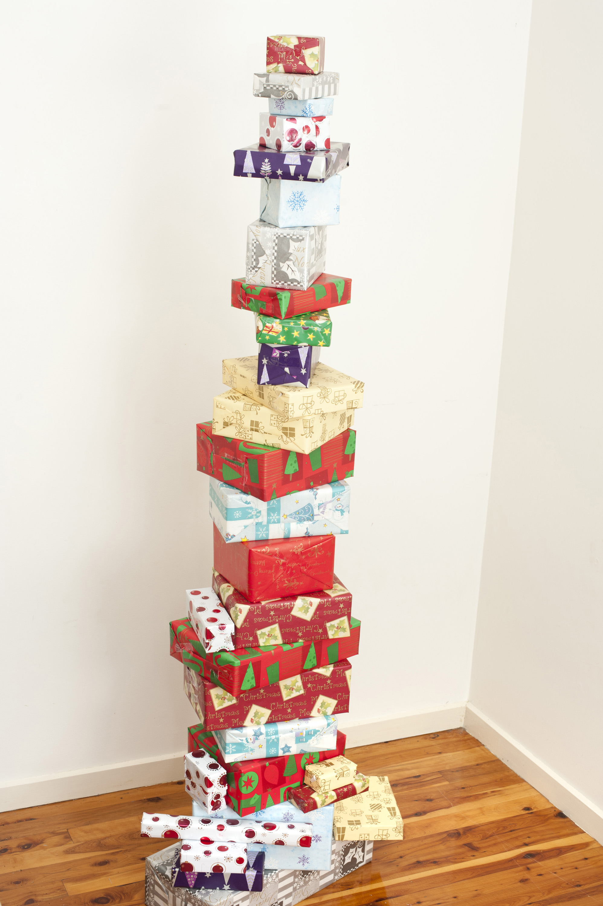 Colourful unique Christmas gift stack with multiple brightly coloured Christmas presents carefully balanced on top of one another in the corner of a room