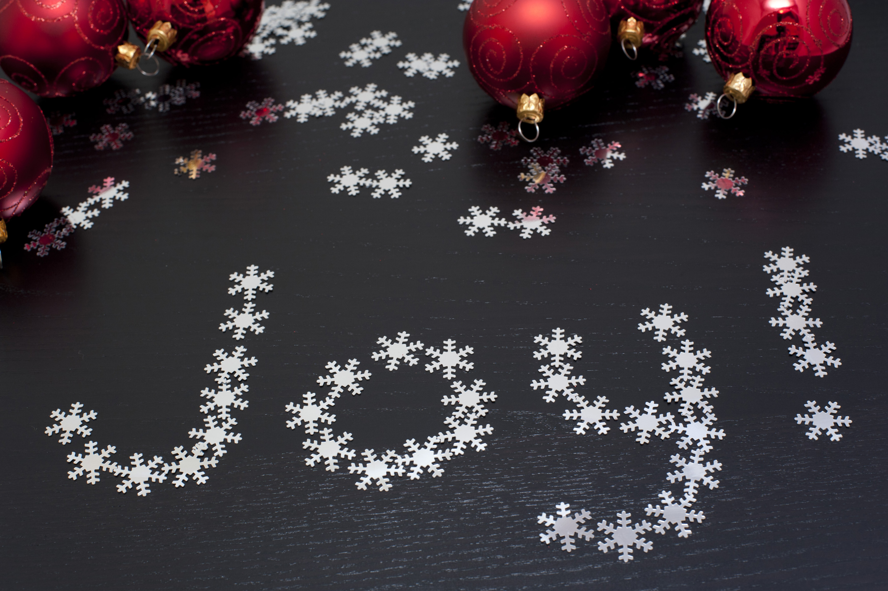 Joy to the world, a Christmas message with the word Joy formed of tiny snowflakes on a dark bqckground