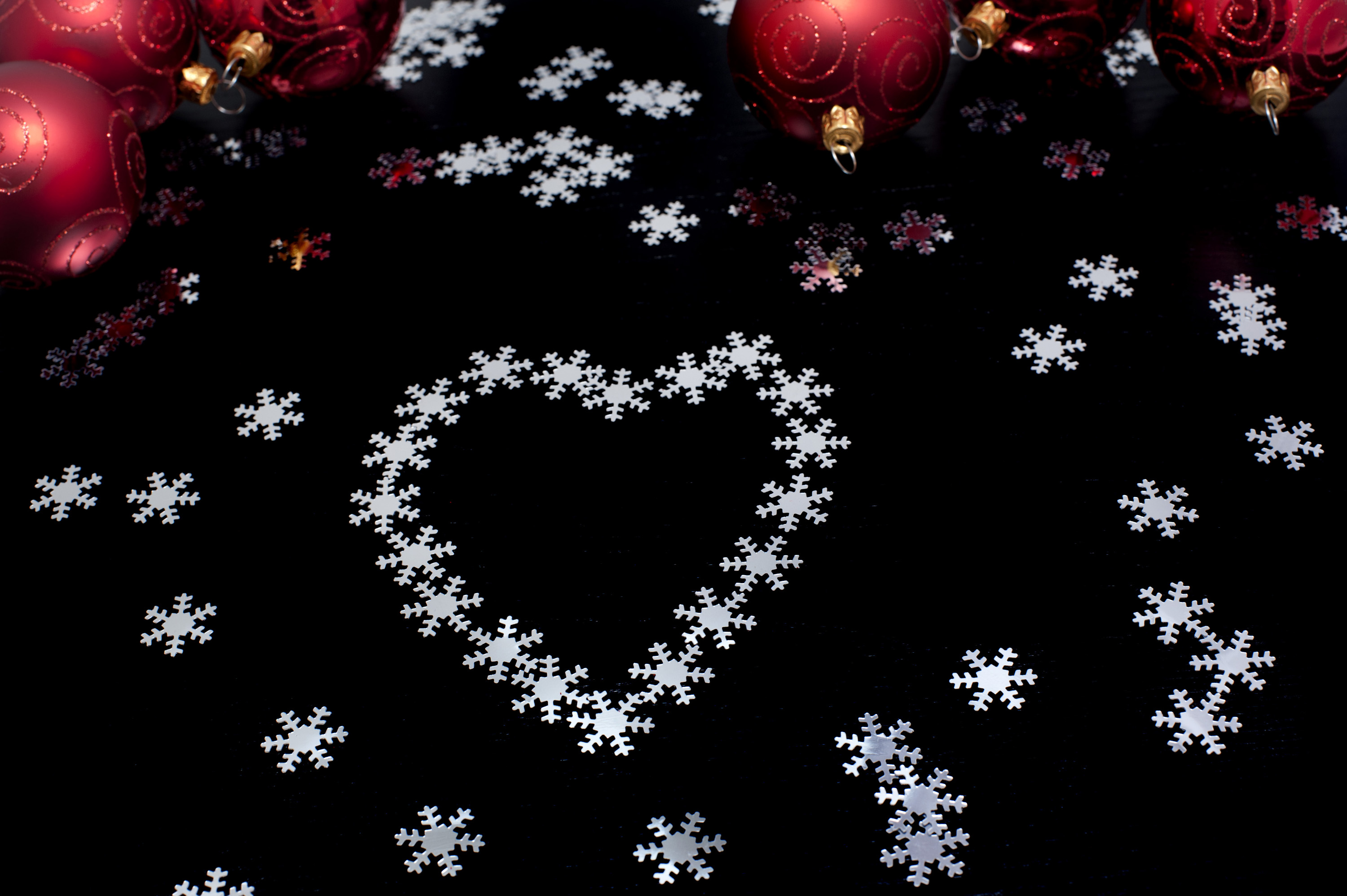 Christmas snowflake heart shape on a black background with scattered snowflakes and colourful Christmas baubles