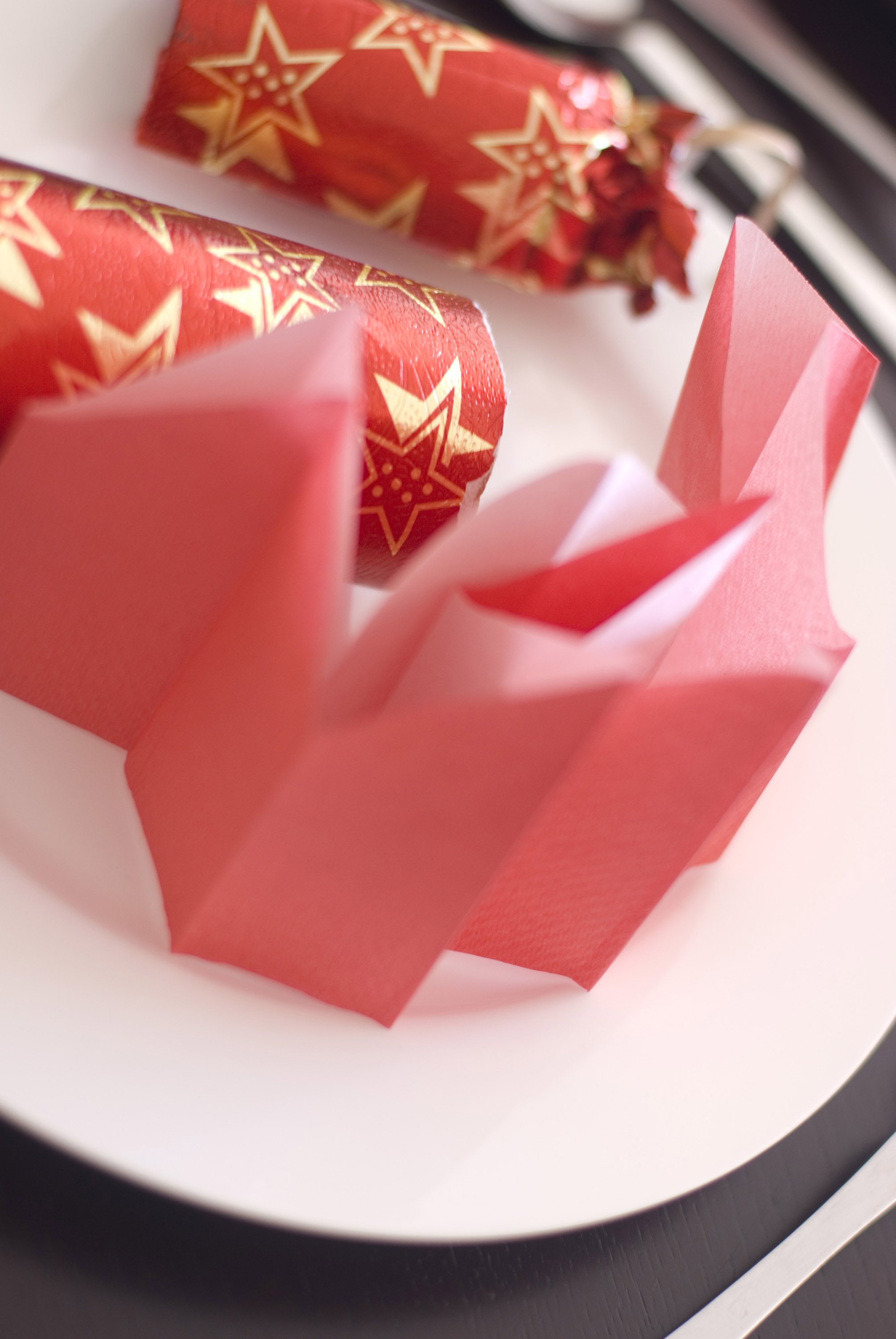 a pulled christmas cracker and red paper party hat