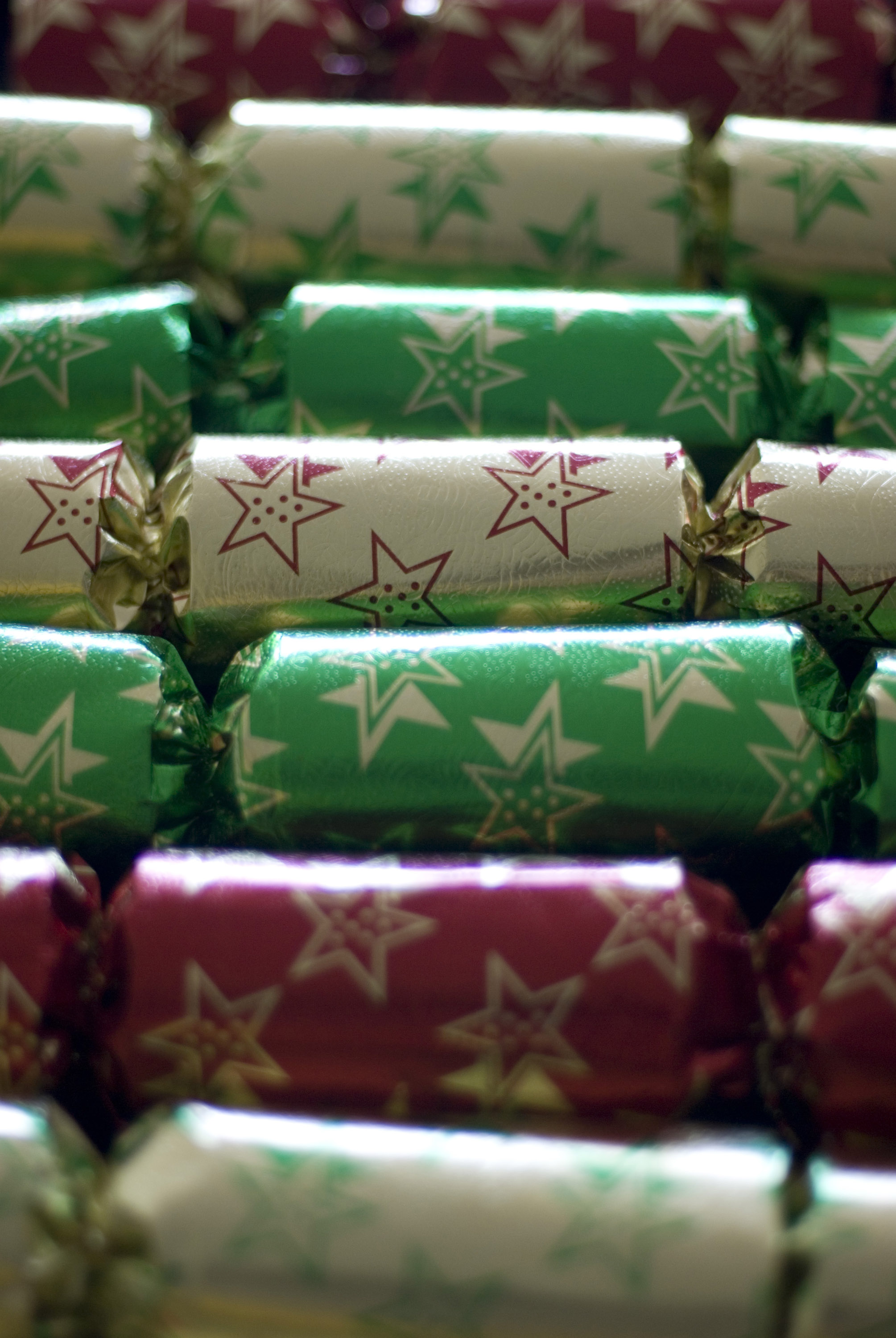 a row of colourful christmas crackers pictured with a narrow depth of field