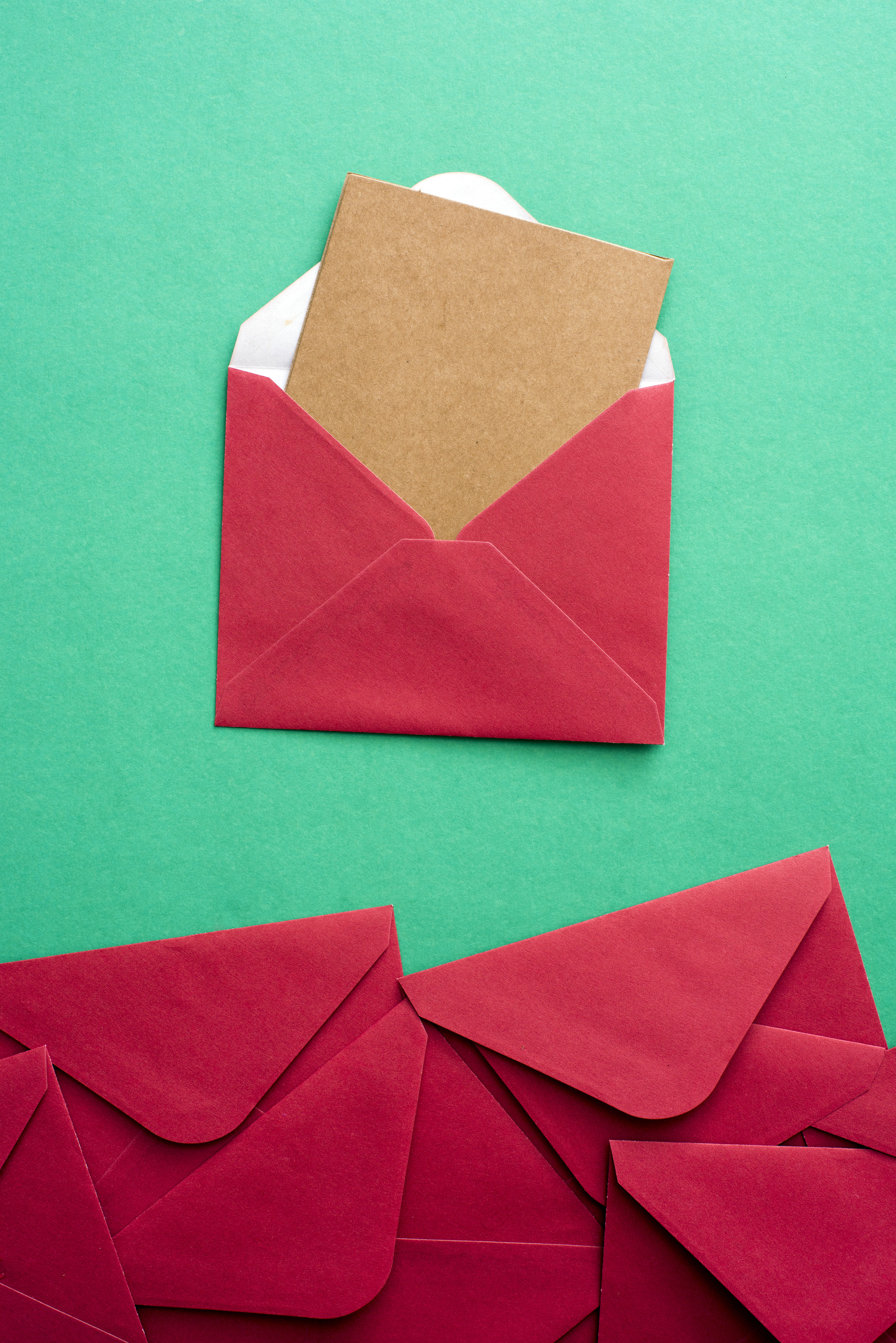 Blank card in festive red Christmas envelope protruding from the open flap with a bottom border of additional stationery over green with copy space for your seasonal greeting